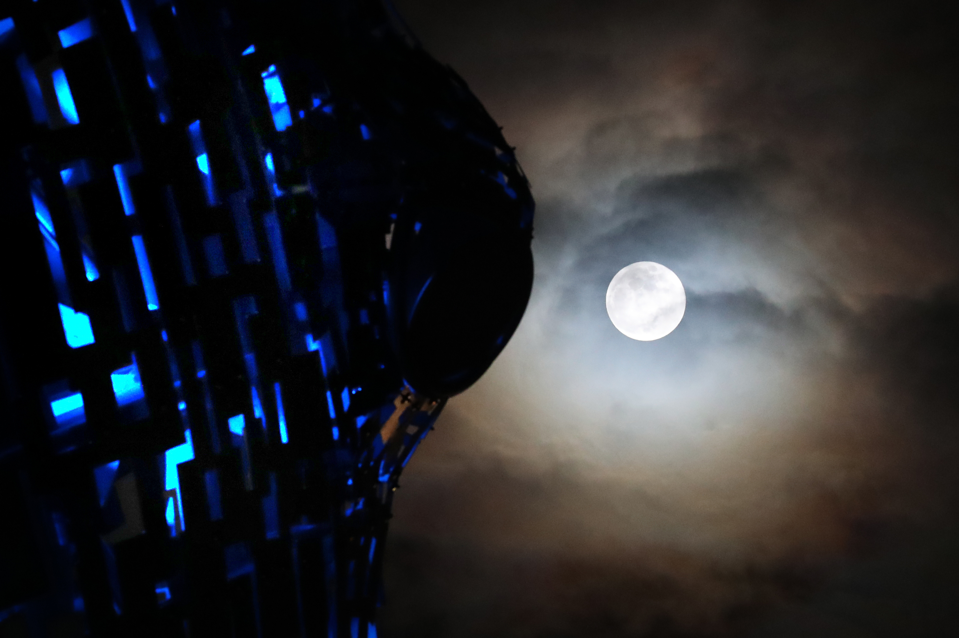 Large bright moon shines down over lit-up Kelpies