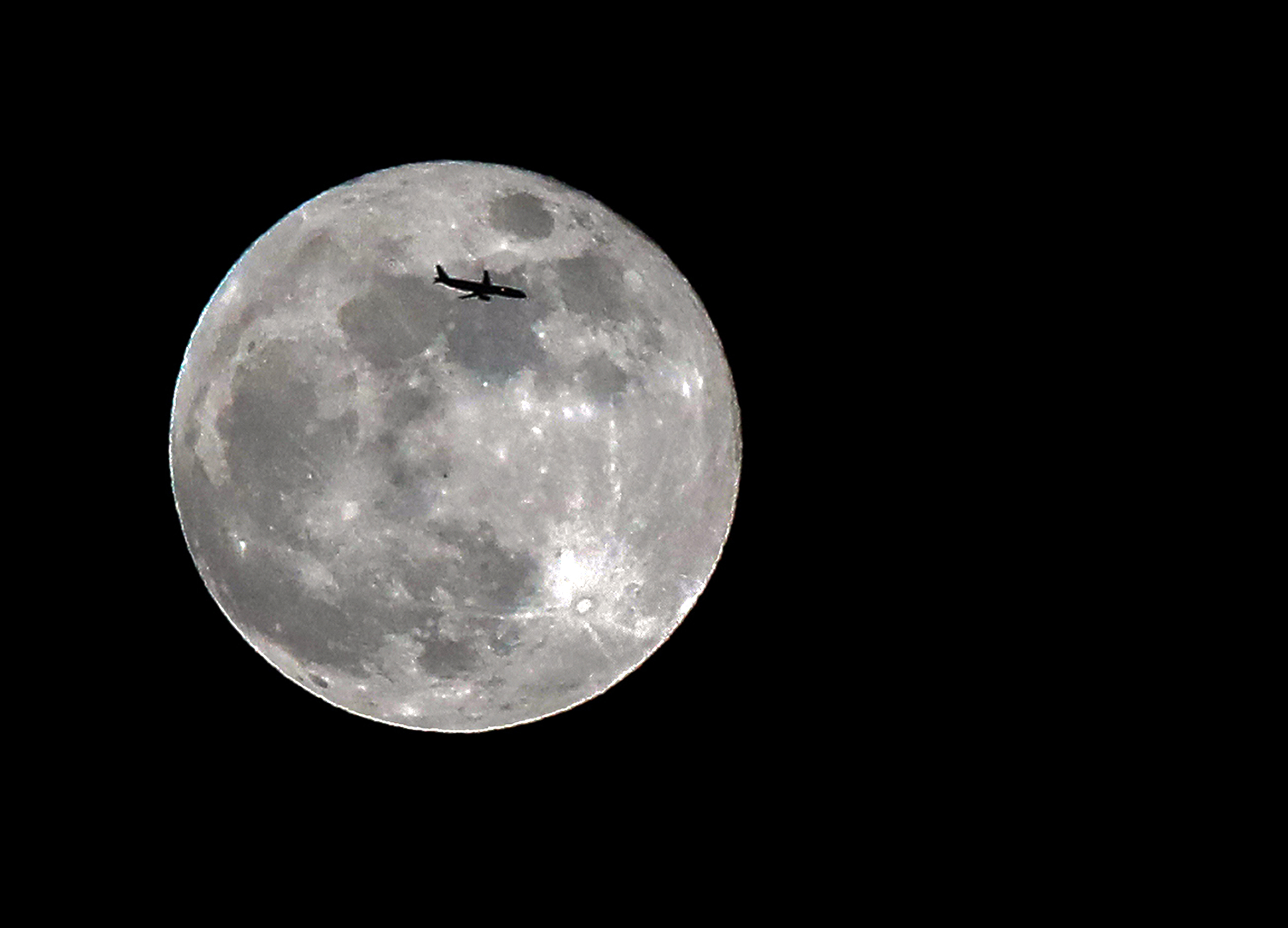 Giant moon silhouetted by passenger jet