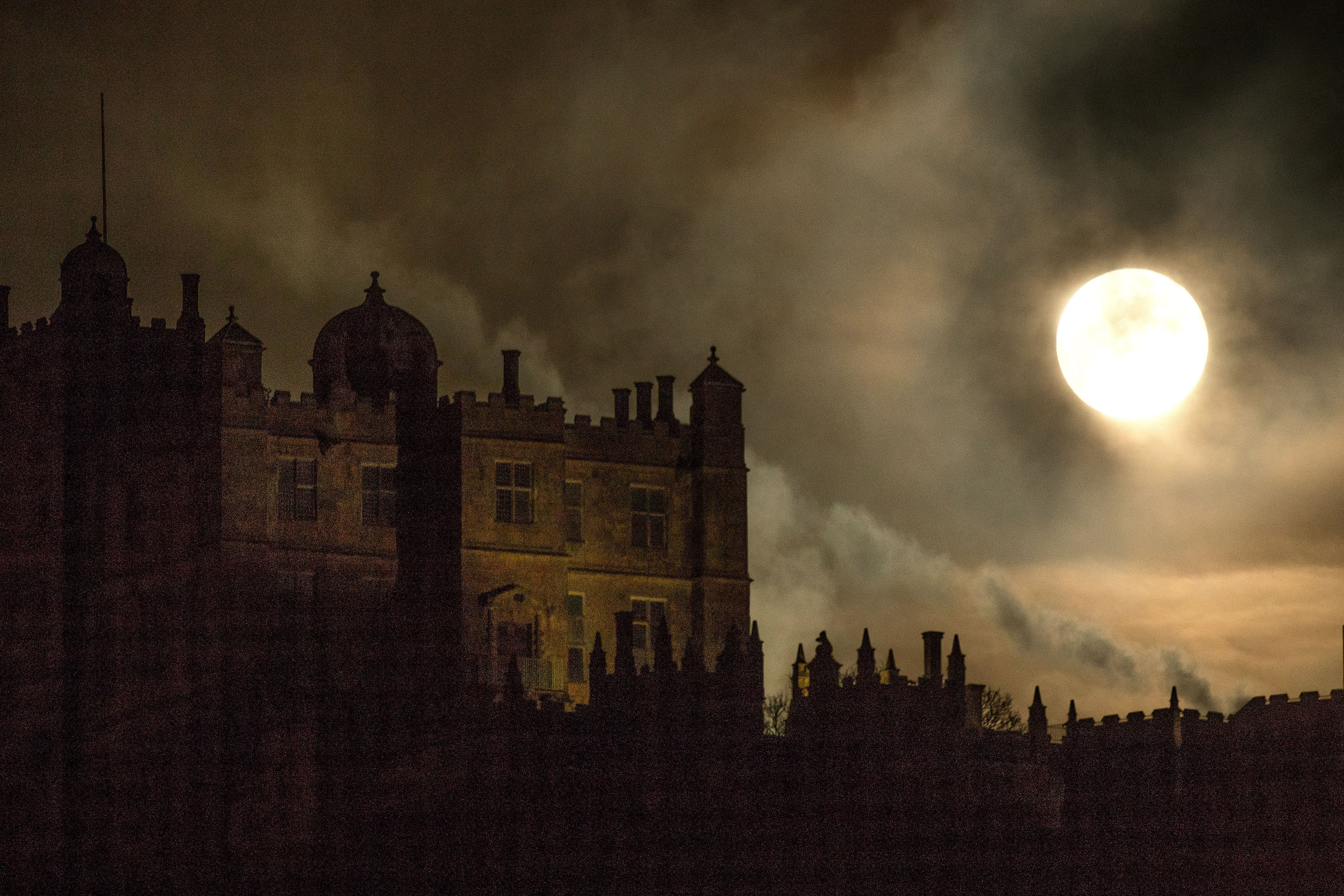 Incredibly bright moon above a stately home