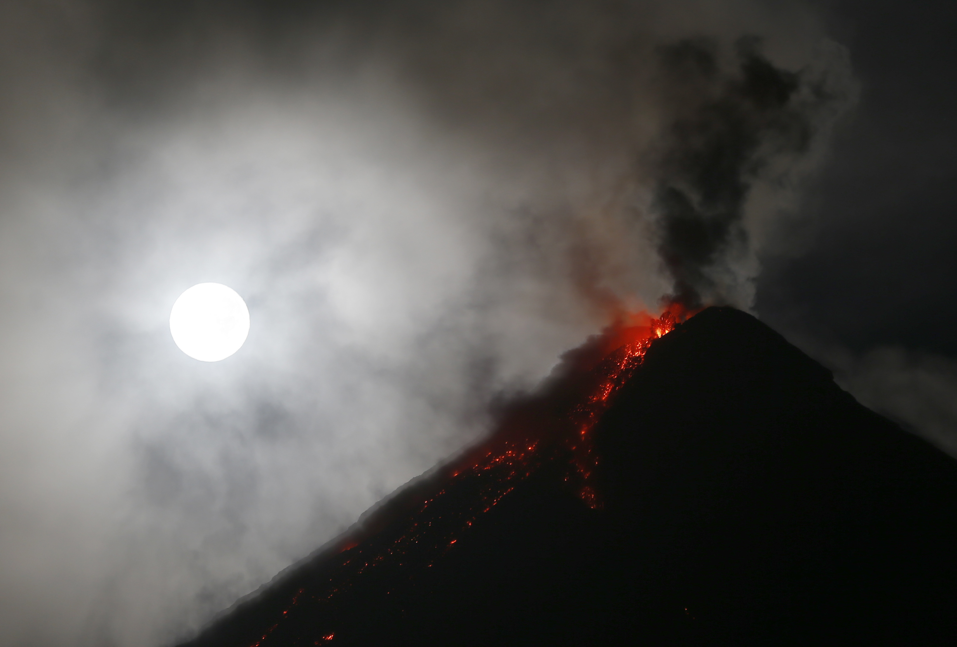 A bright white moon shines above erupting volcano