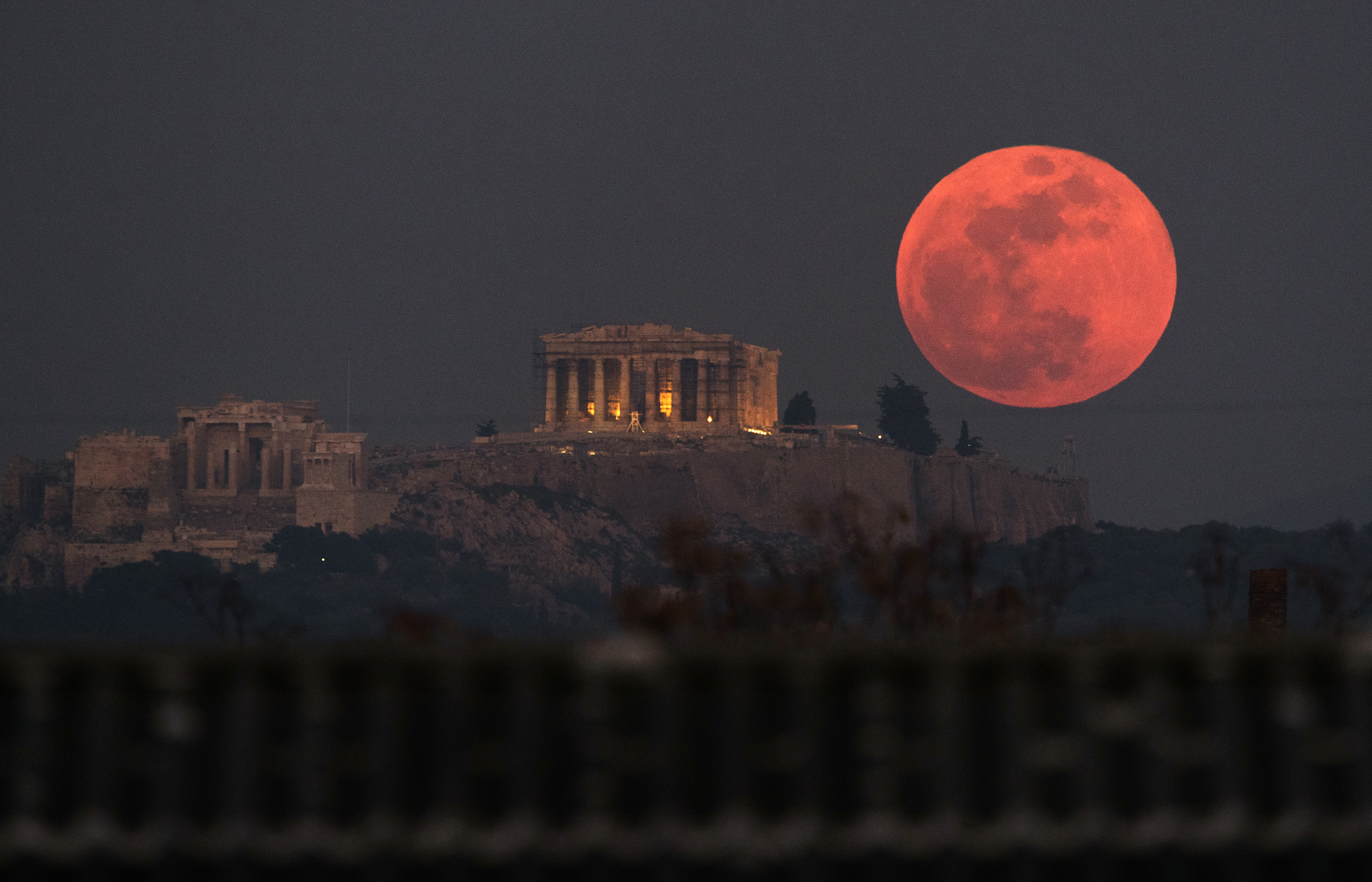 A super blue blood moon rises behind the Parthenon temple on the Acropolis of Athens, Greece (Petros Giannakouris/PA)