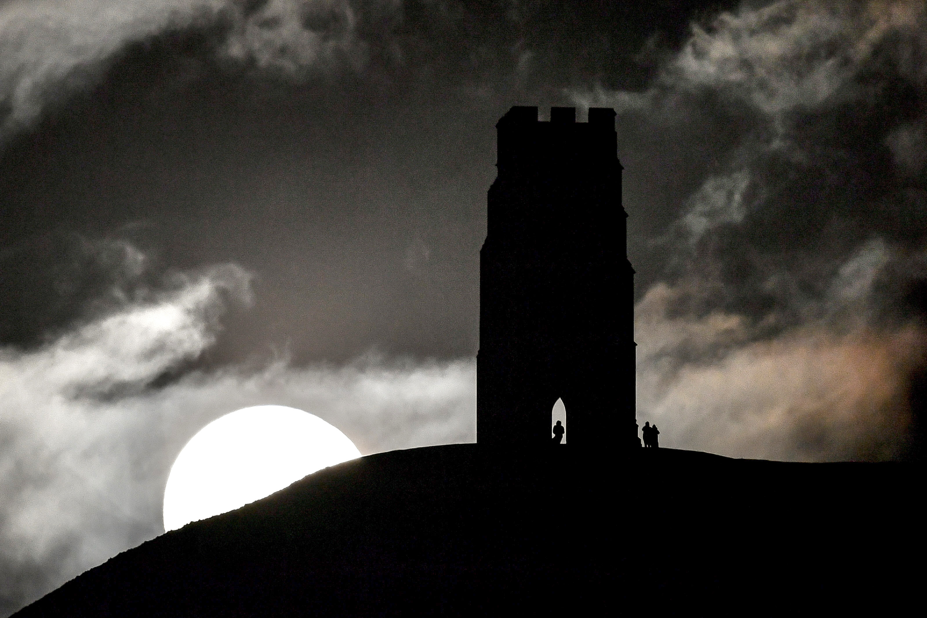 Large white moon rises above the hill Glastonbury Tor sits on