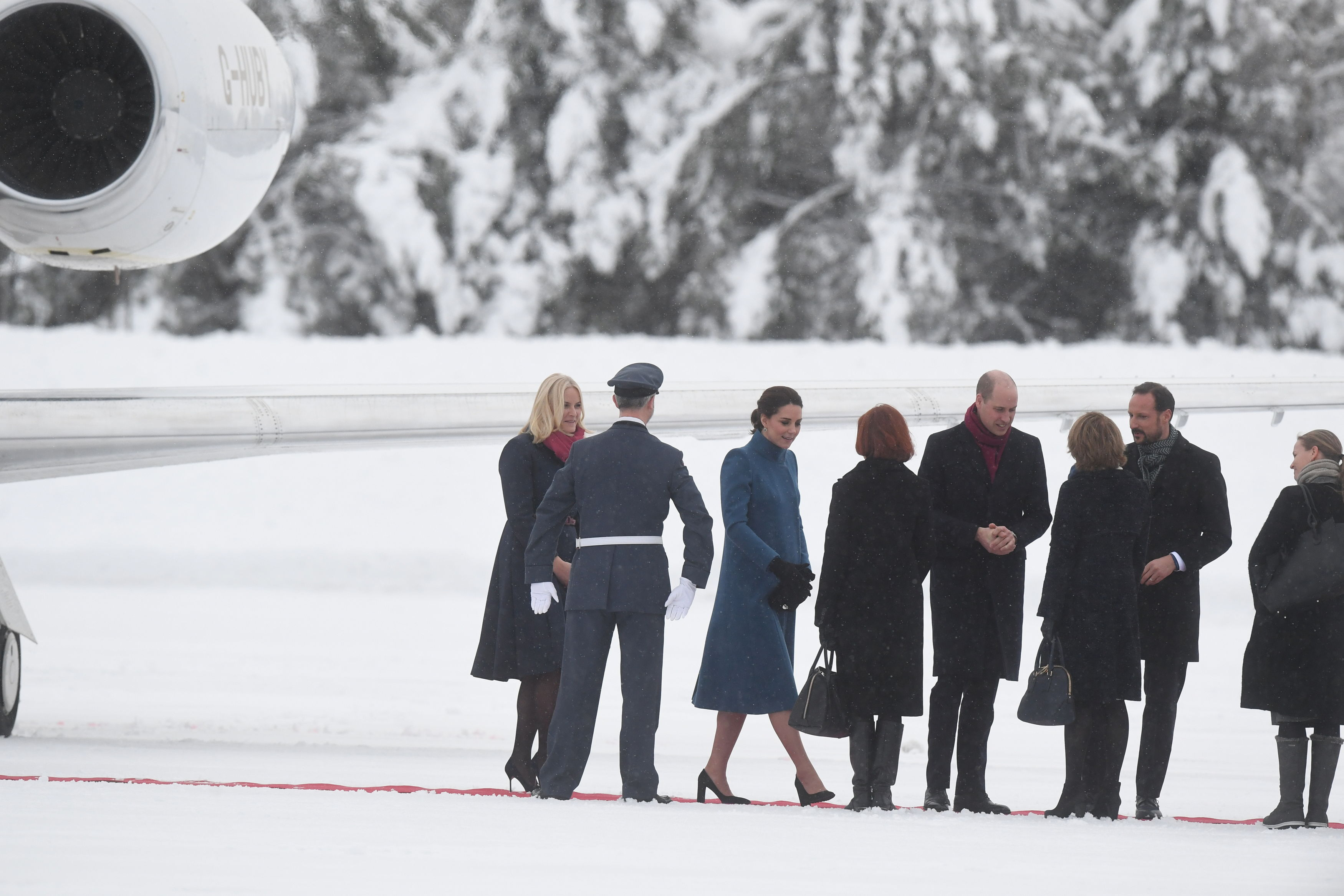 The Cambridges are introduced to dignitaries at the airport (Victoria Jones/PA)