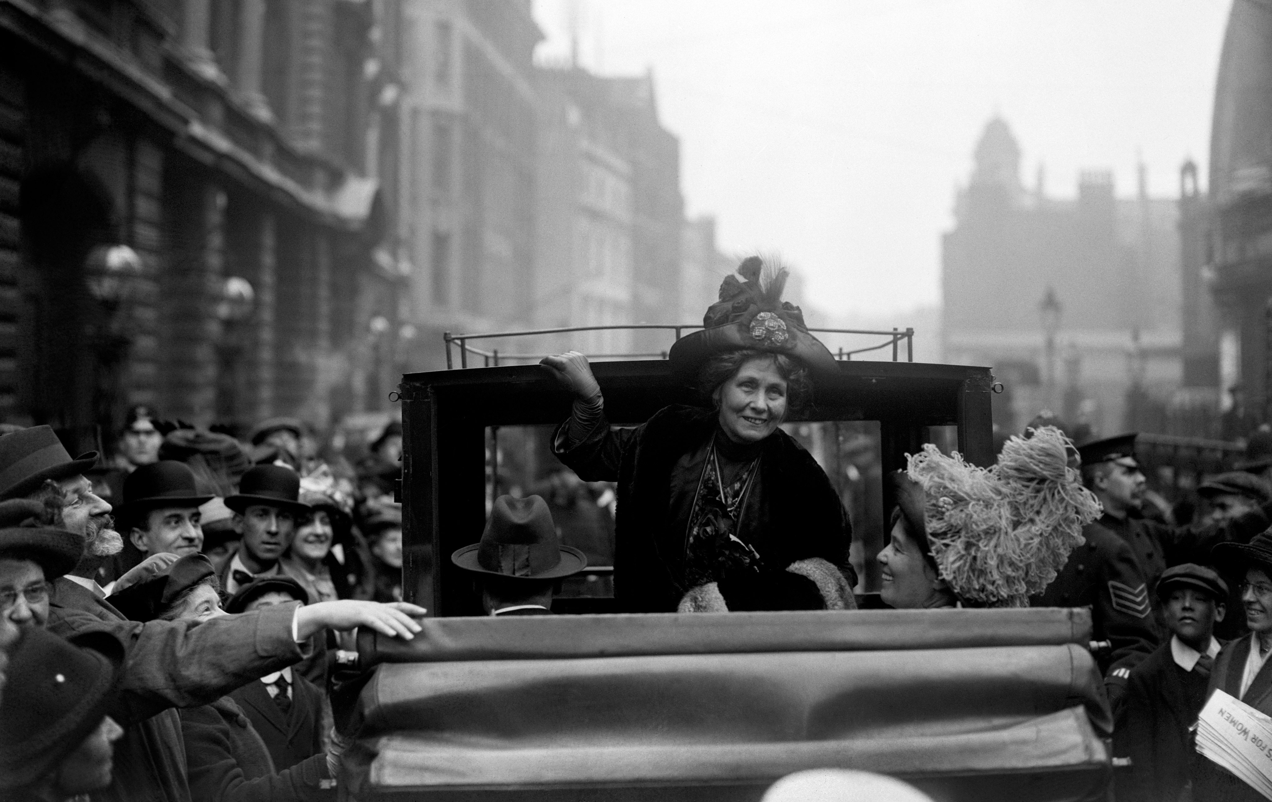 Woman smiling from the back of a carriage, with crowds of onlookers