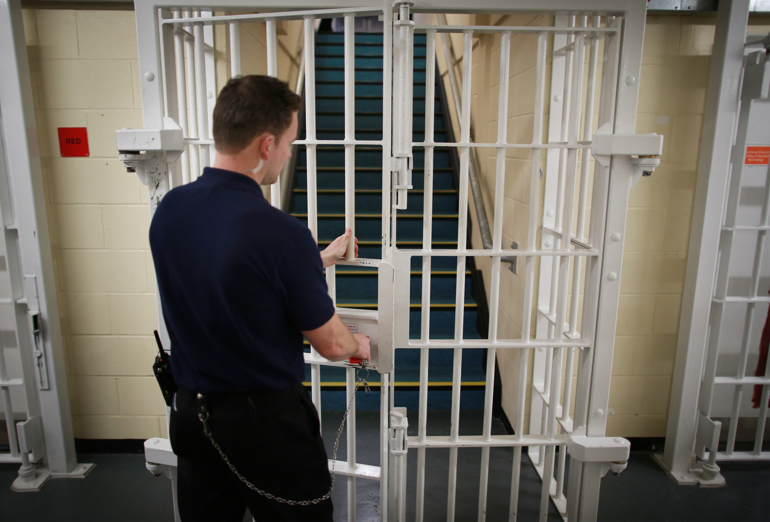 A prison guard closes a door in a prison