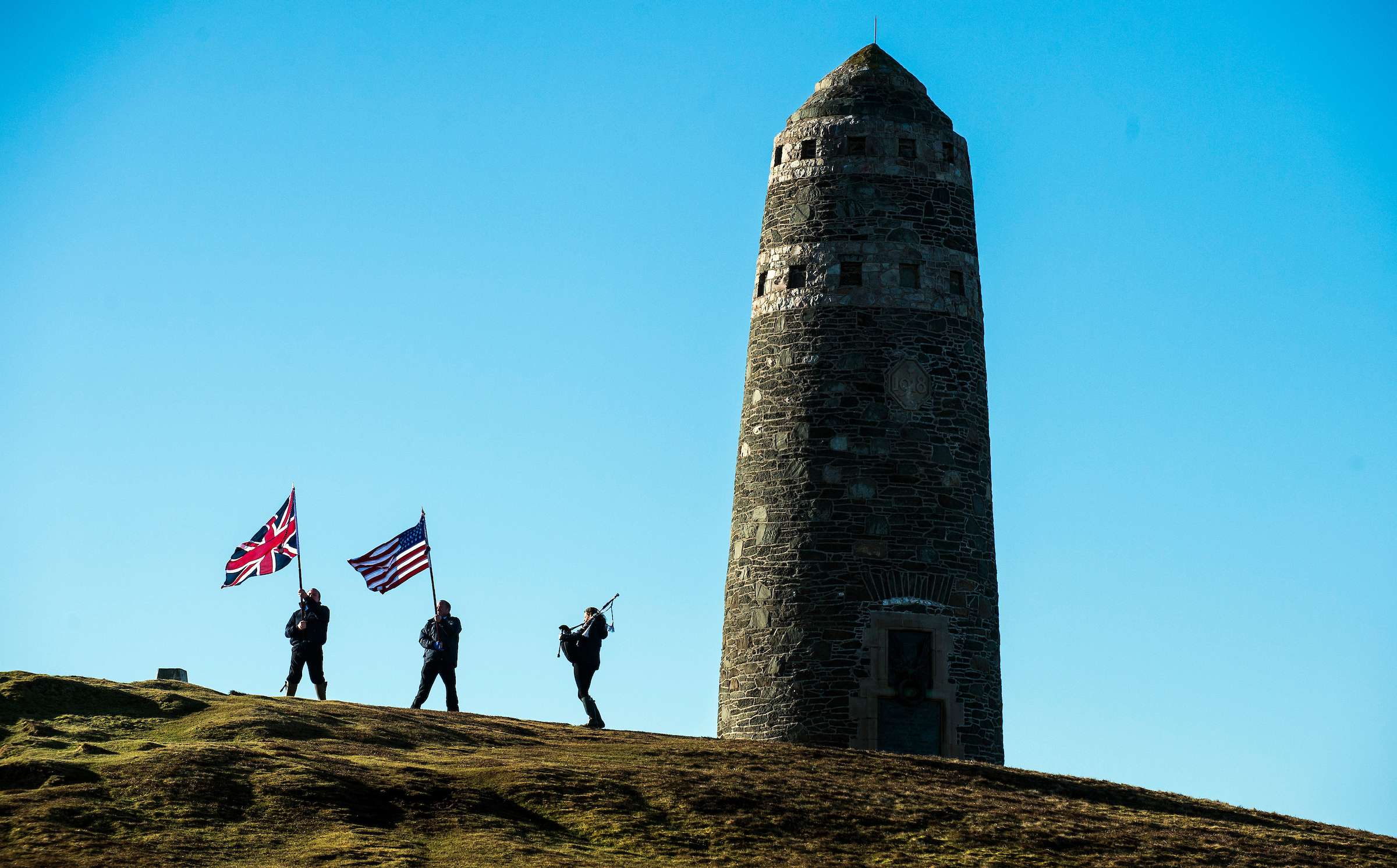 The UK and American flags are flown as a piper plays next to the American Monument on Islay (Lenny Warren/Warren Media)