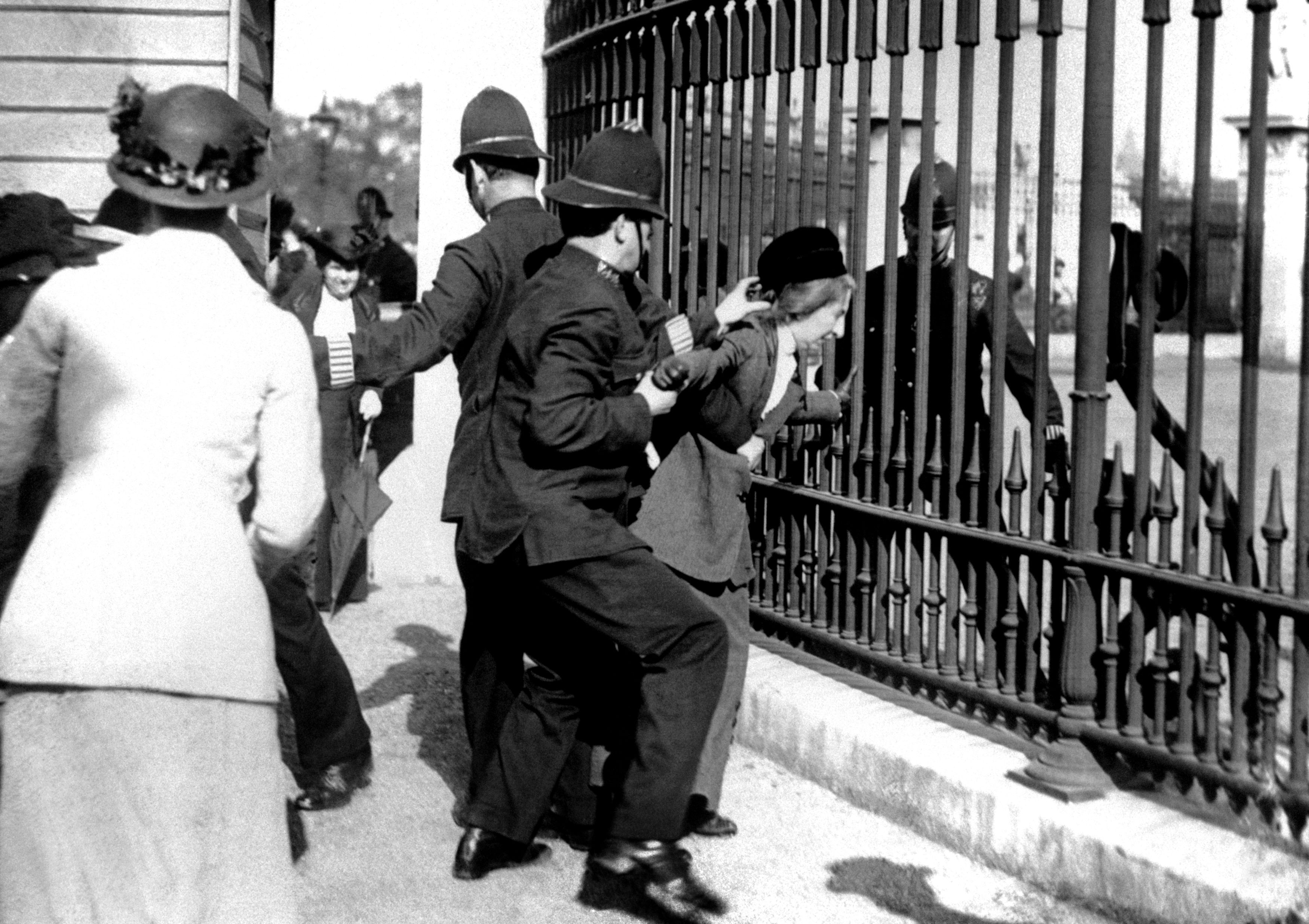 A policeman restraining a demonstrator in 1914 as suffragettes gathered outside Buckingham Palace (PA)