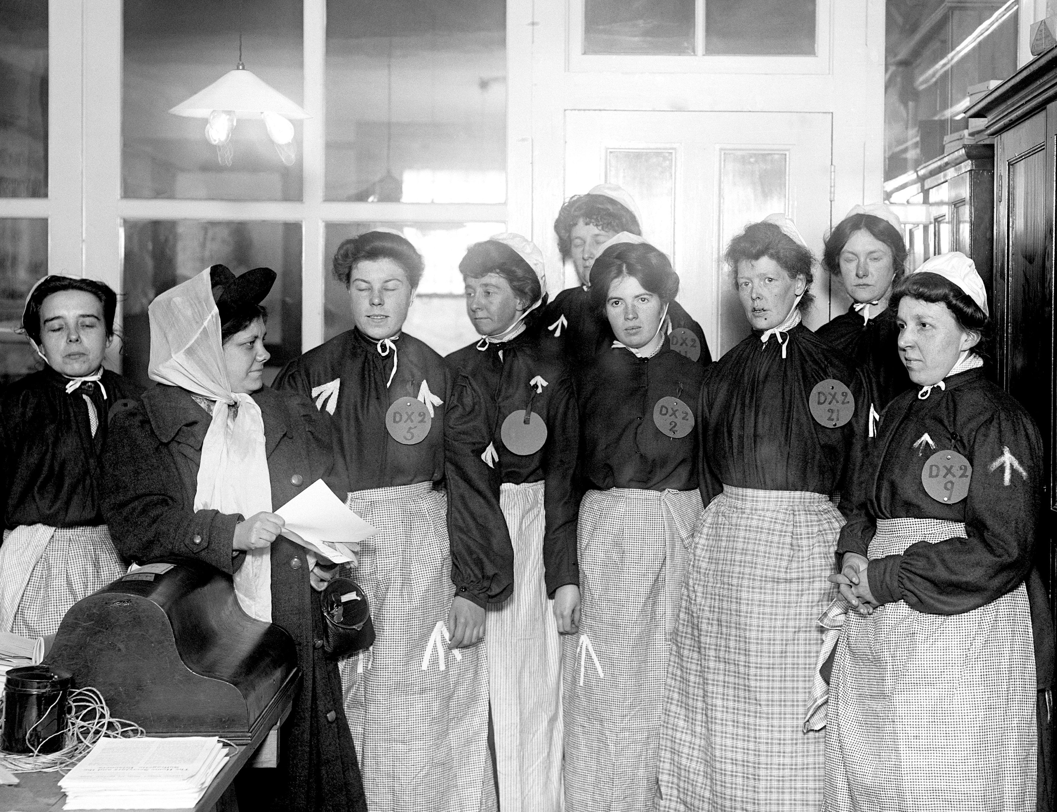 Flora Drummond, left. giving instructions to suffragettes dressed as prisoners in 1908 (PA)
