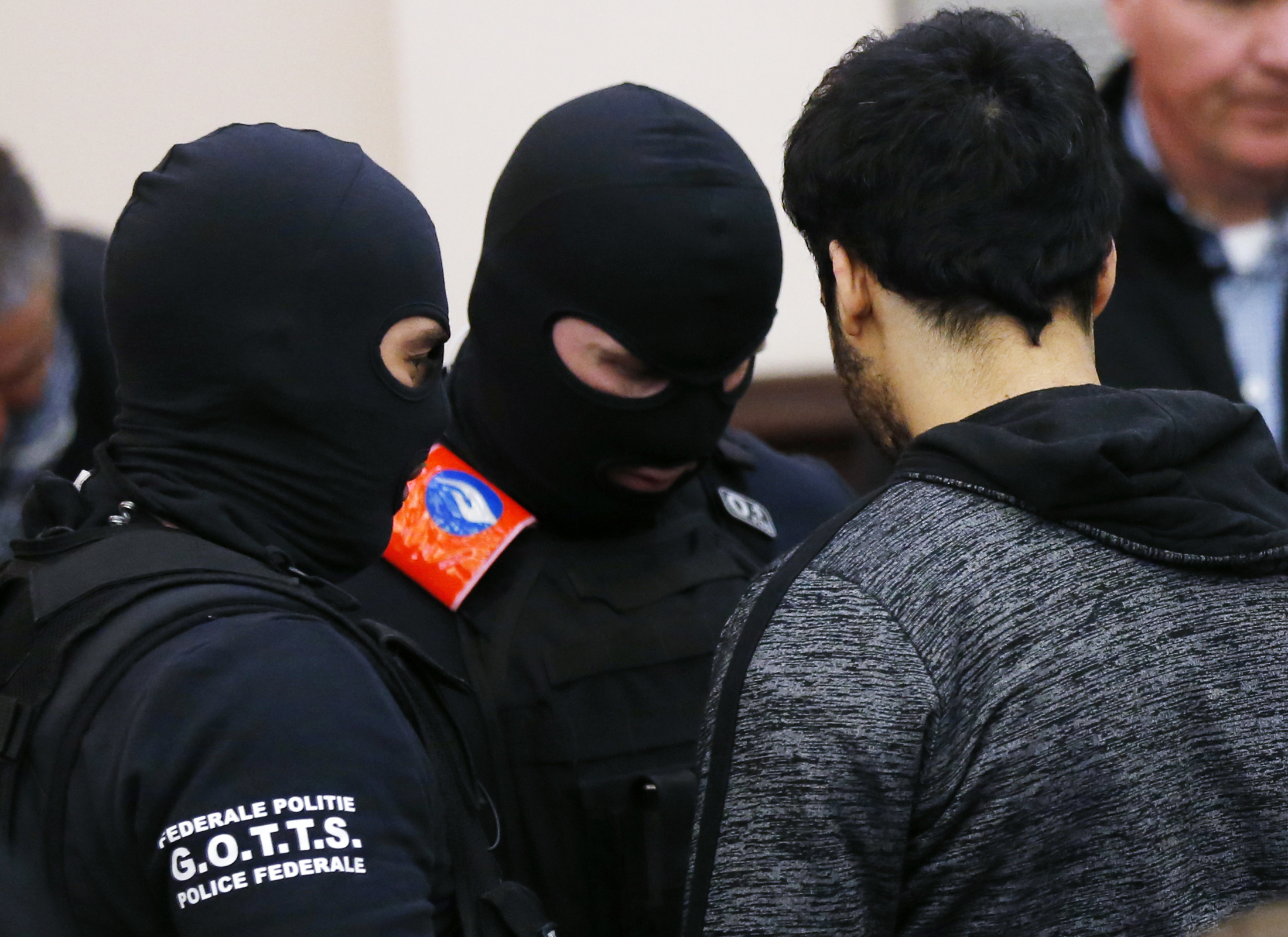 Soufiane Ayari, right, is surrounded by Belgian special police officers during the second day of the trial (Francois Lenoir, Pool Photo via AP)