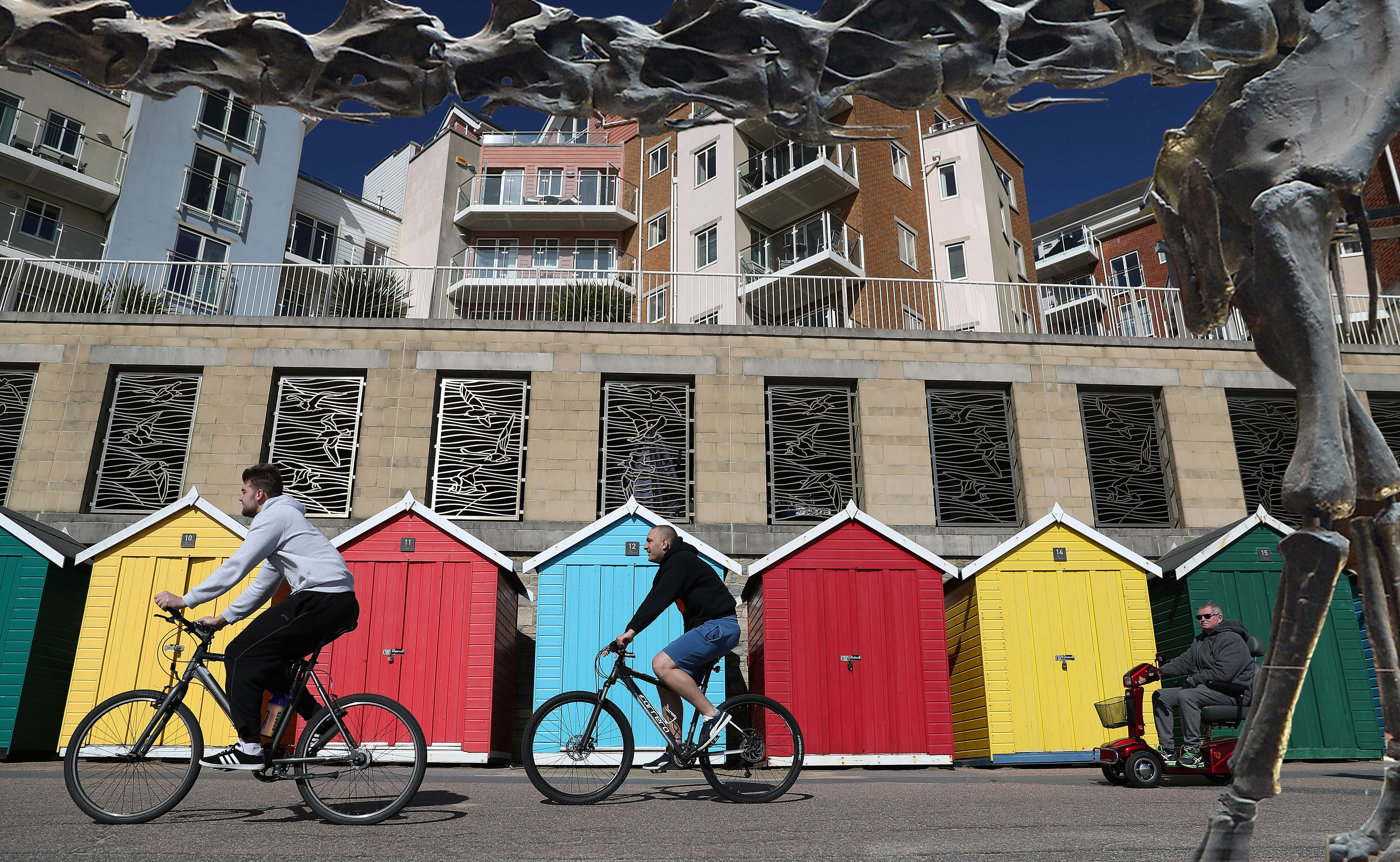 People make their way past multi-coloured beach huts on Boscombe beach in Bournemouth