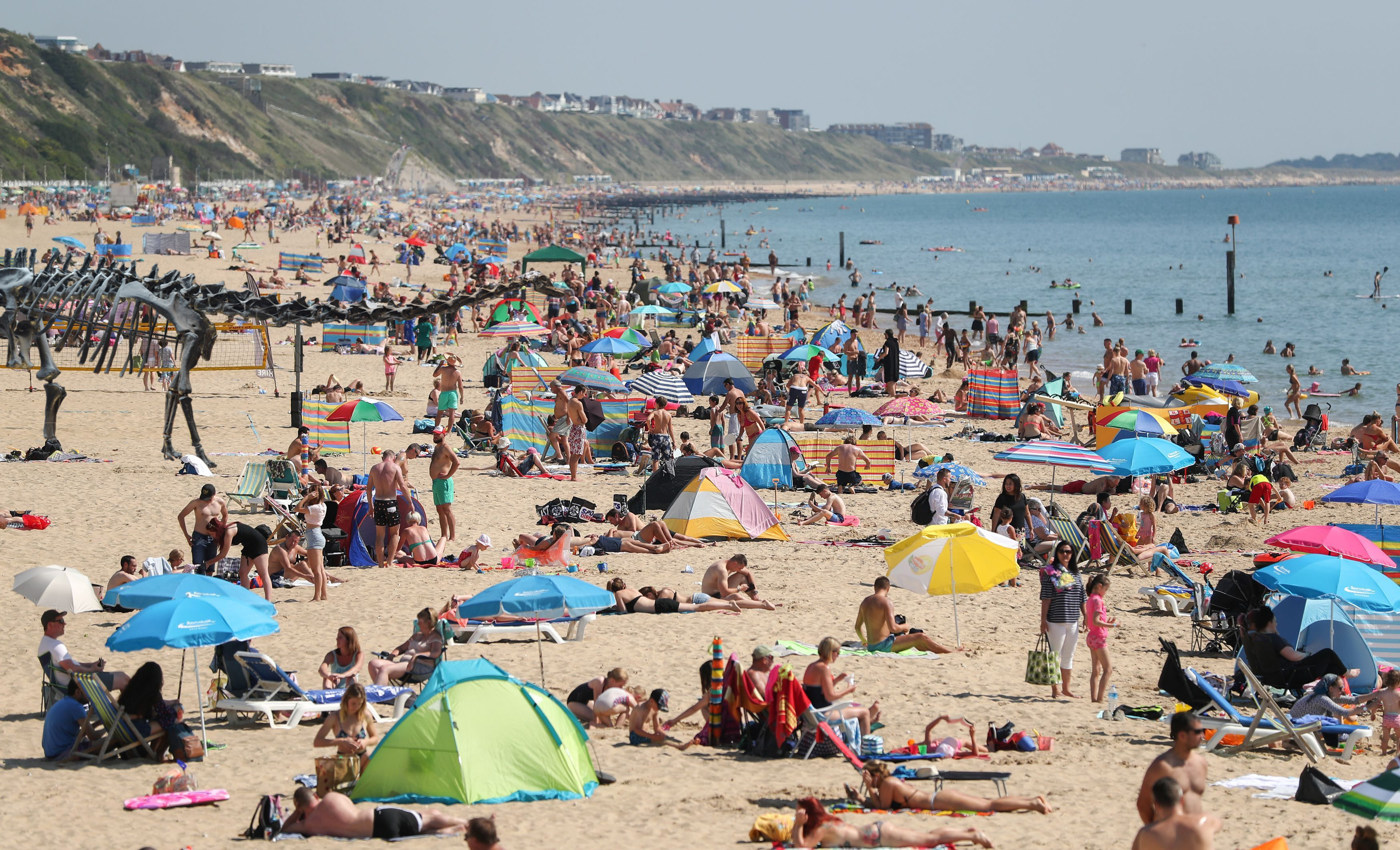 People sunbathe on Boscombe beach in Dorset, as Britons enjoy predicted highs of 27C (81F) after a wet and cool August.