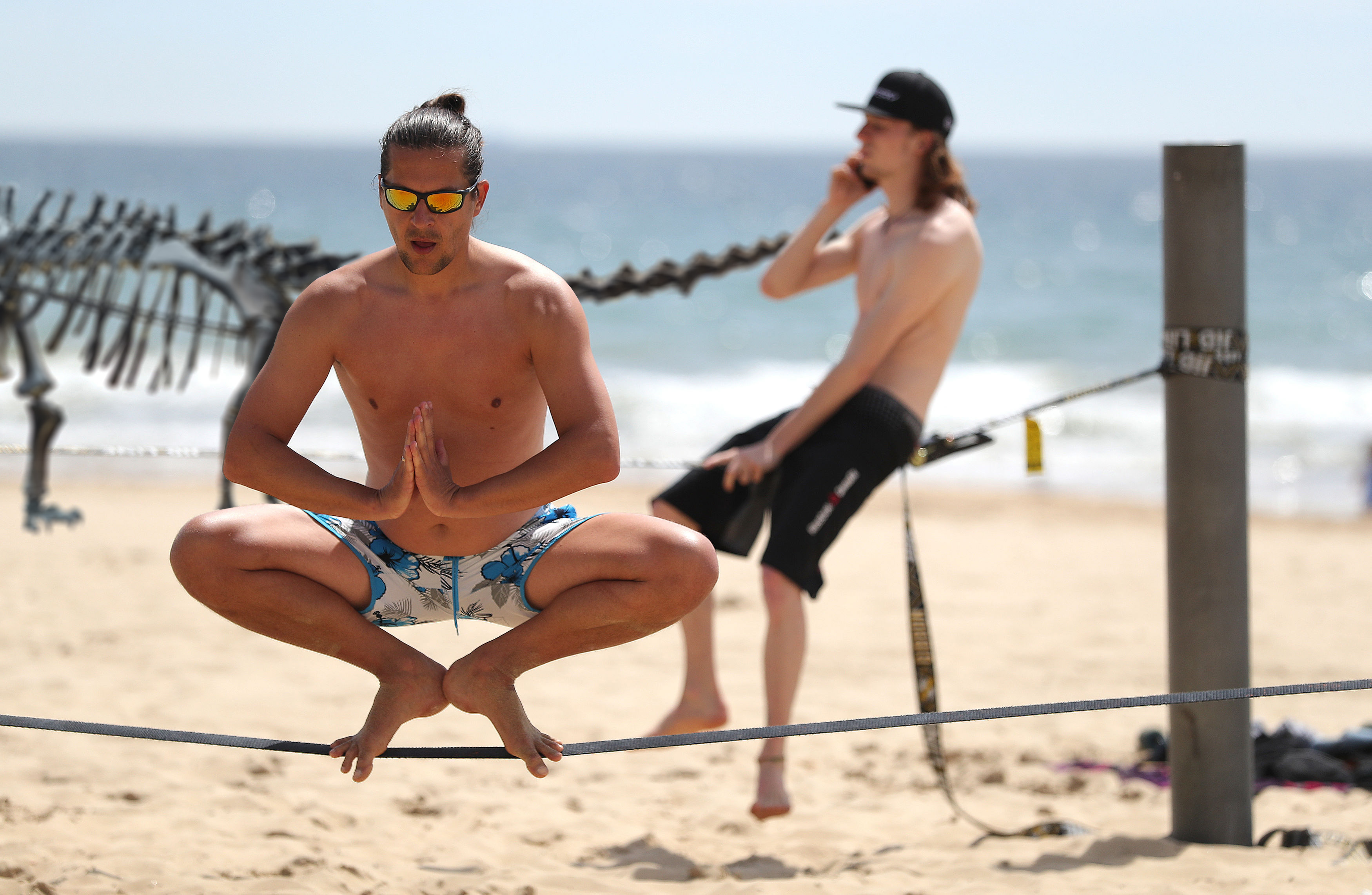 Two slackliners practice on Bournemouth beach in Dorset as forecasters predict that a wave of warm air will move across the country in the coming days.