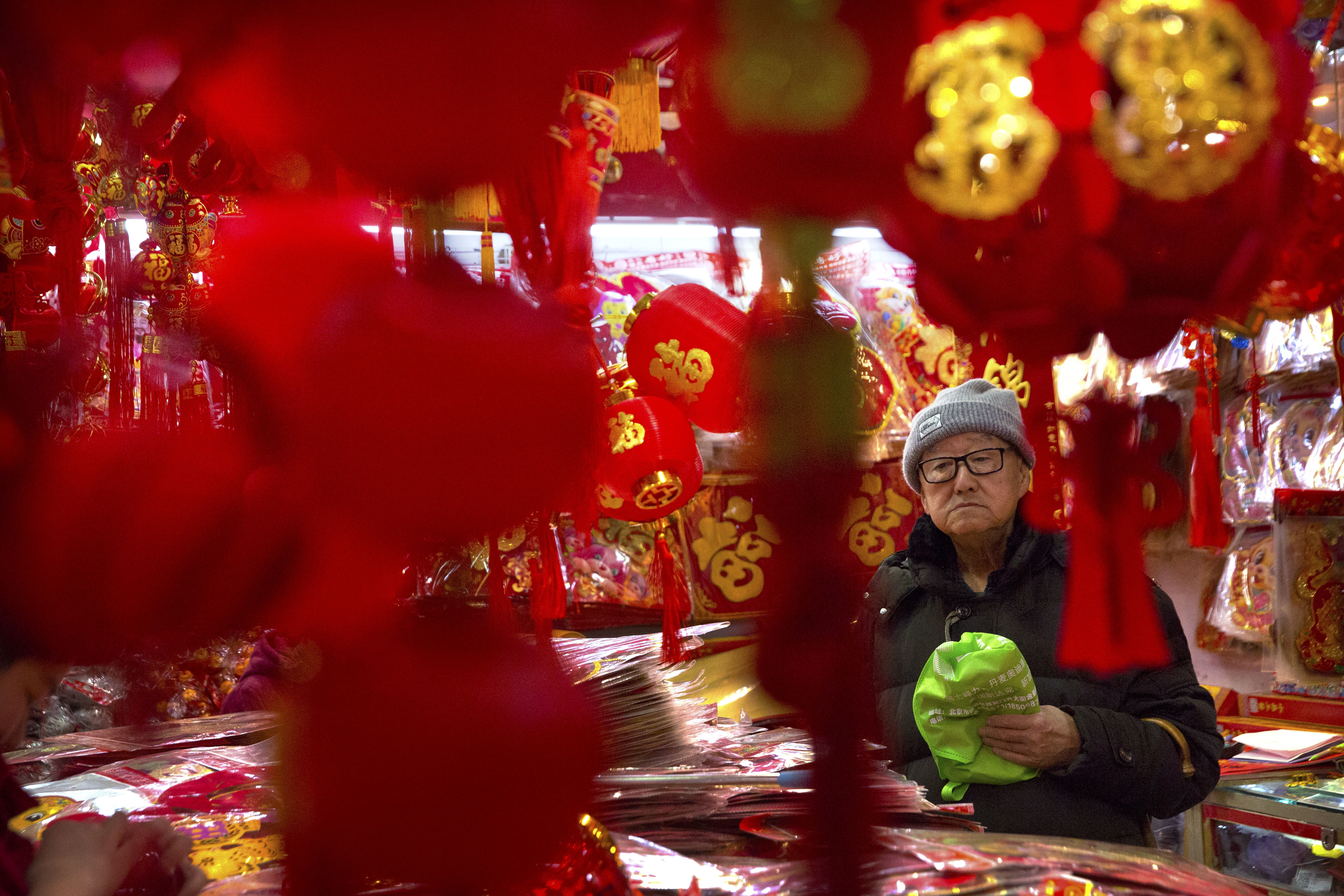 A customer shops for Lunar New Year decorations at a wholesale market in Beijing (Mark Schiefelbein/AP)