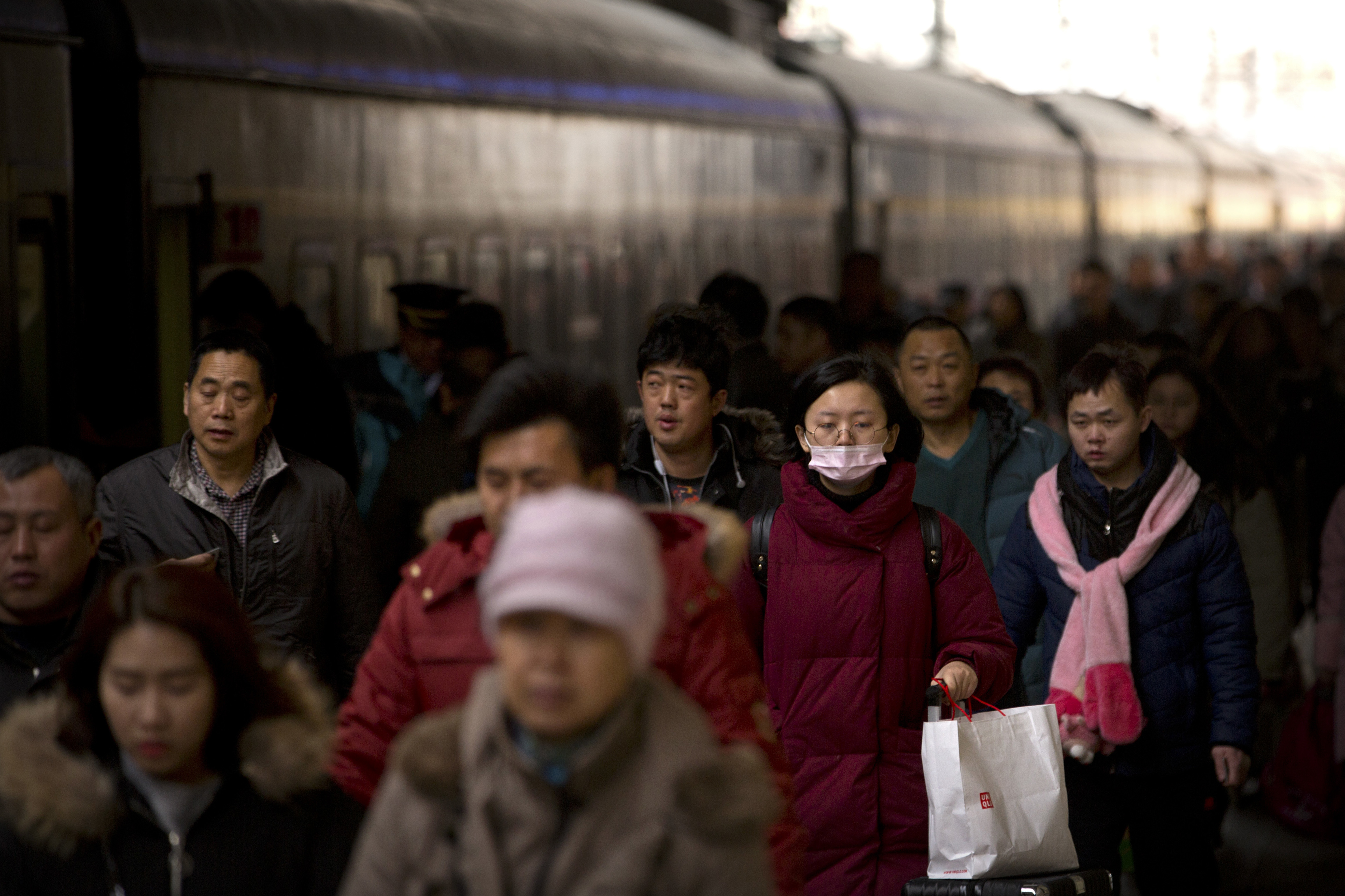 People walk to board a train at the Beijing Railway Station (Mark Schiefelbein/AP)