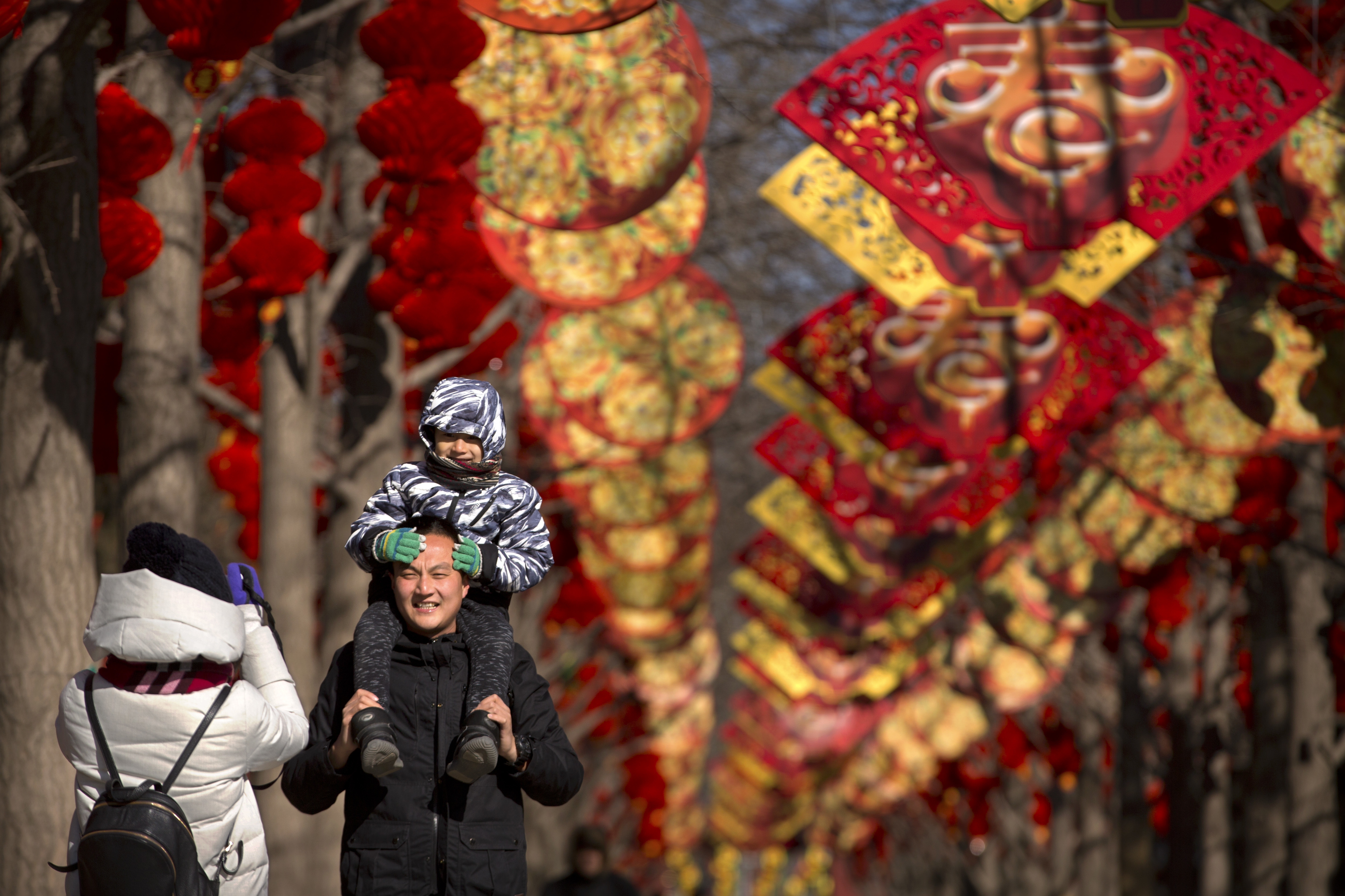 A man holds a child as they pose for a photo near a pathway decorated for the Lunar New Year (Mark Schiefelbein/AP)