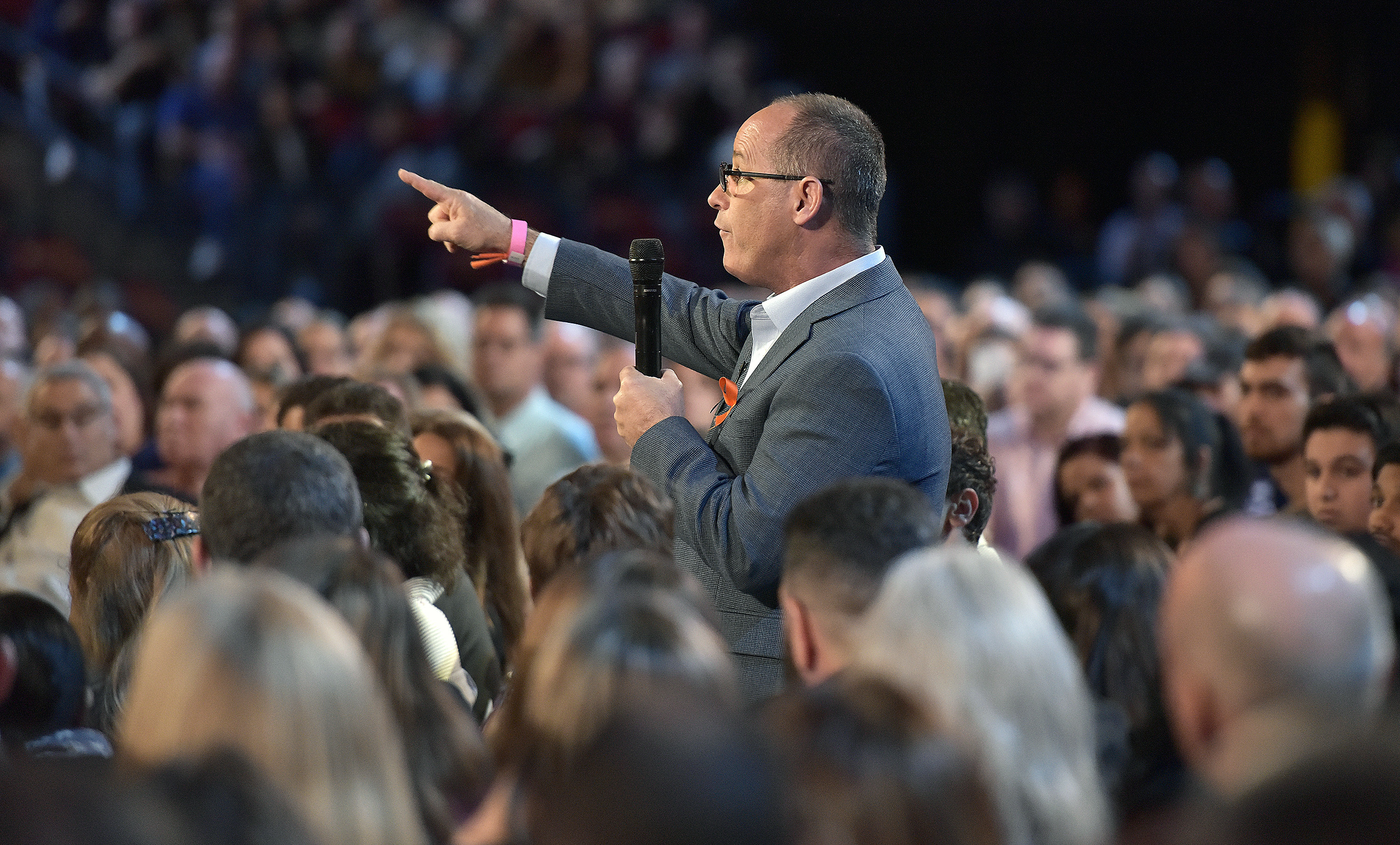 Man in the audience stands up to ask a question in a microphone pointing up to the stage