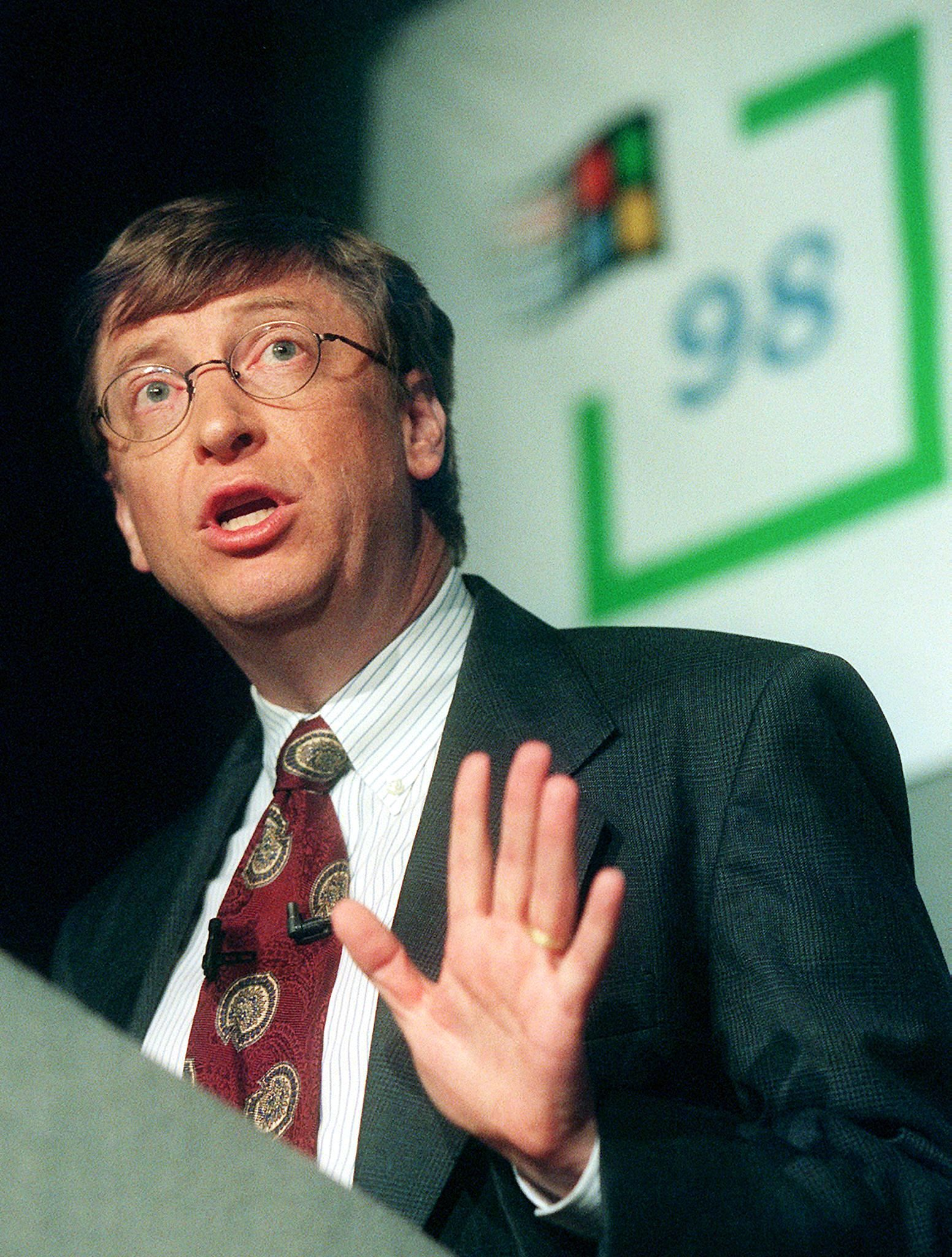 A younger Gates speaks at a platform with the Windows 98 logo behind him