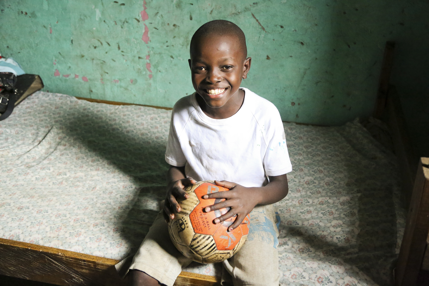 A child holds a football donated by PARK Social Soccer Co