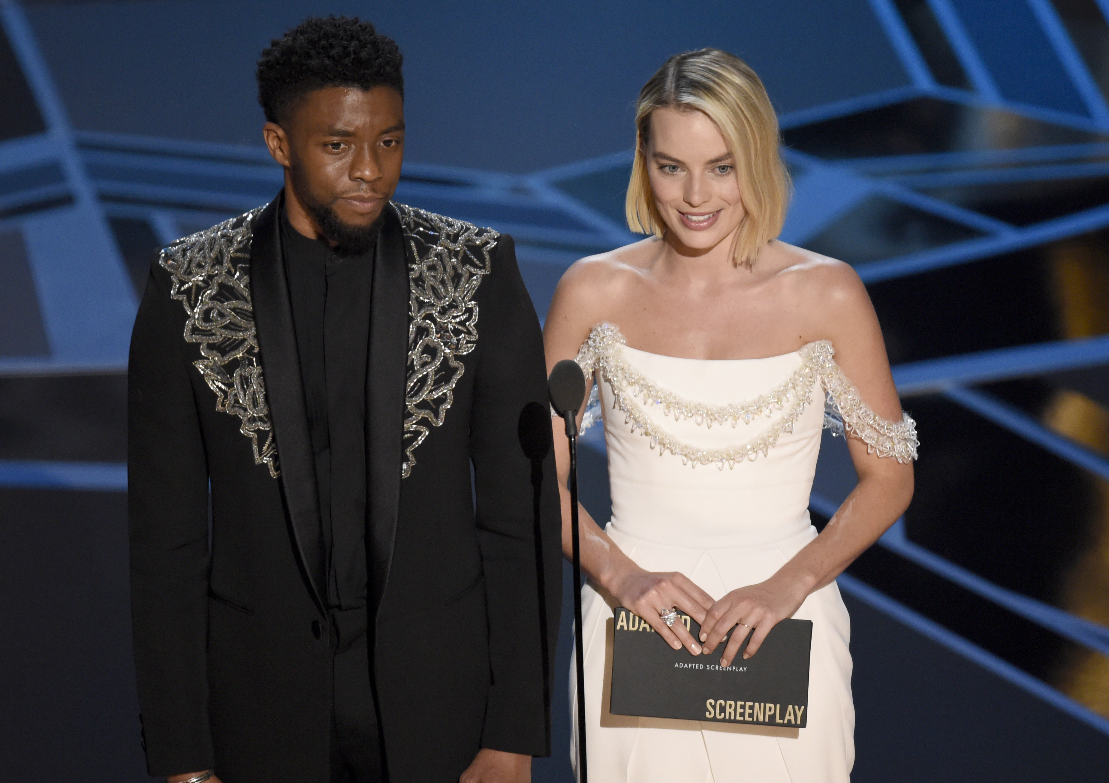 Chadwick Boseman, left, and Margot Robbie present the award for best adapted screenplay at the Oscars 2018