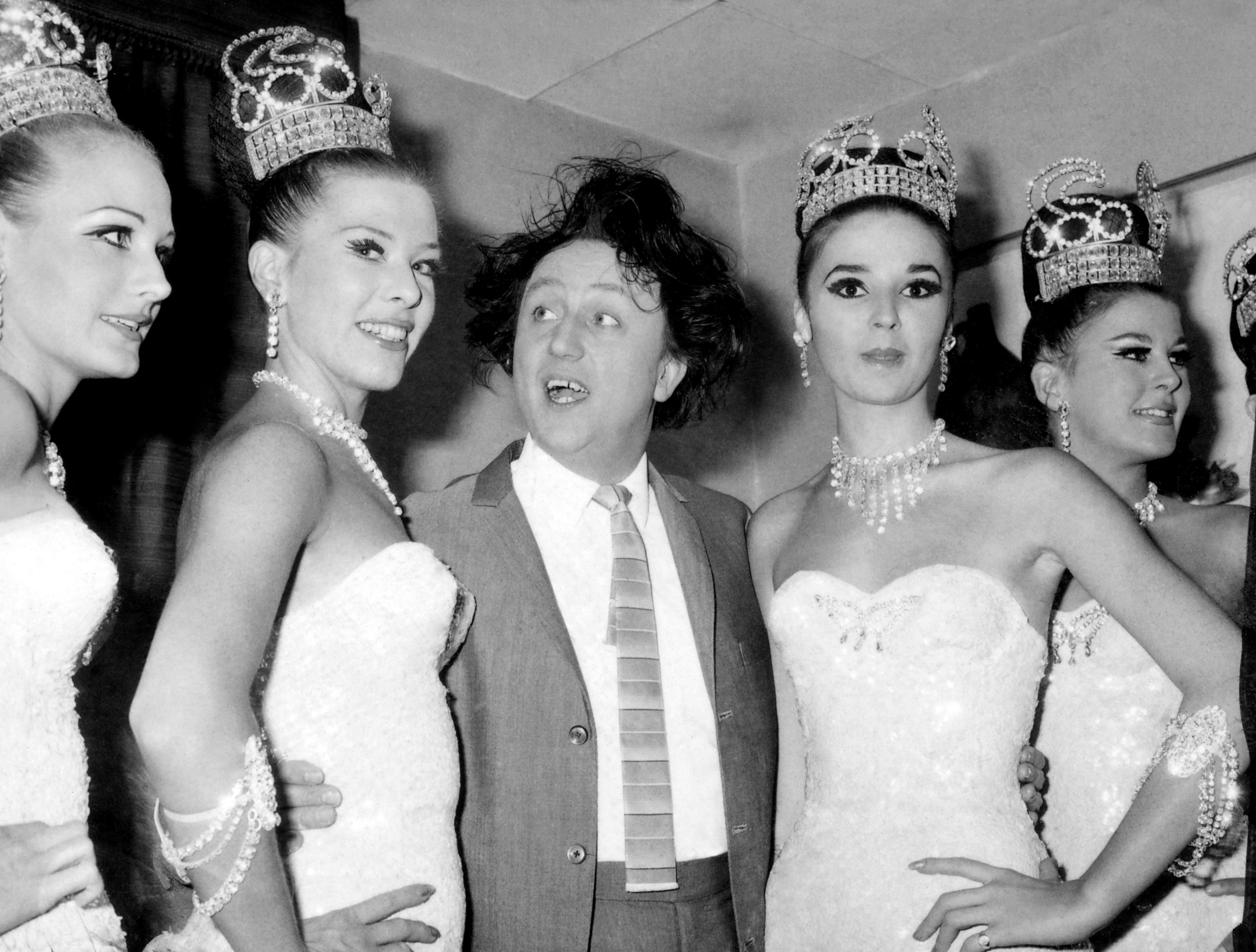 Ken Dodd poses backstage with the Bluebell Girls in 1976 (PA)