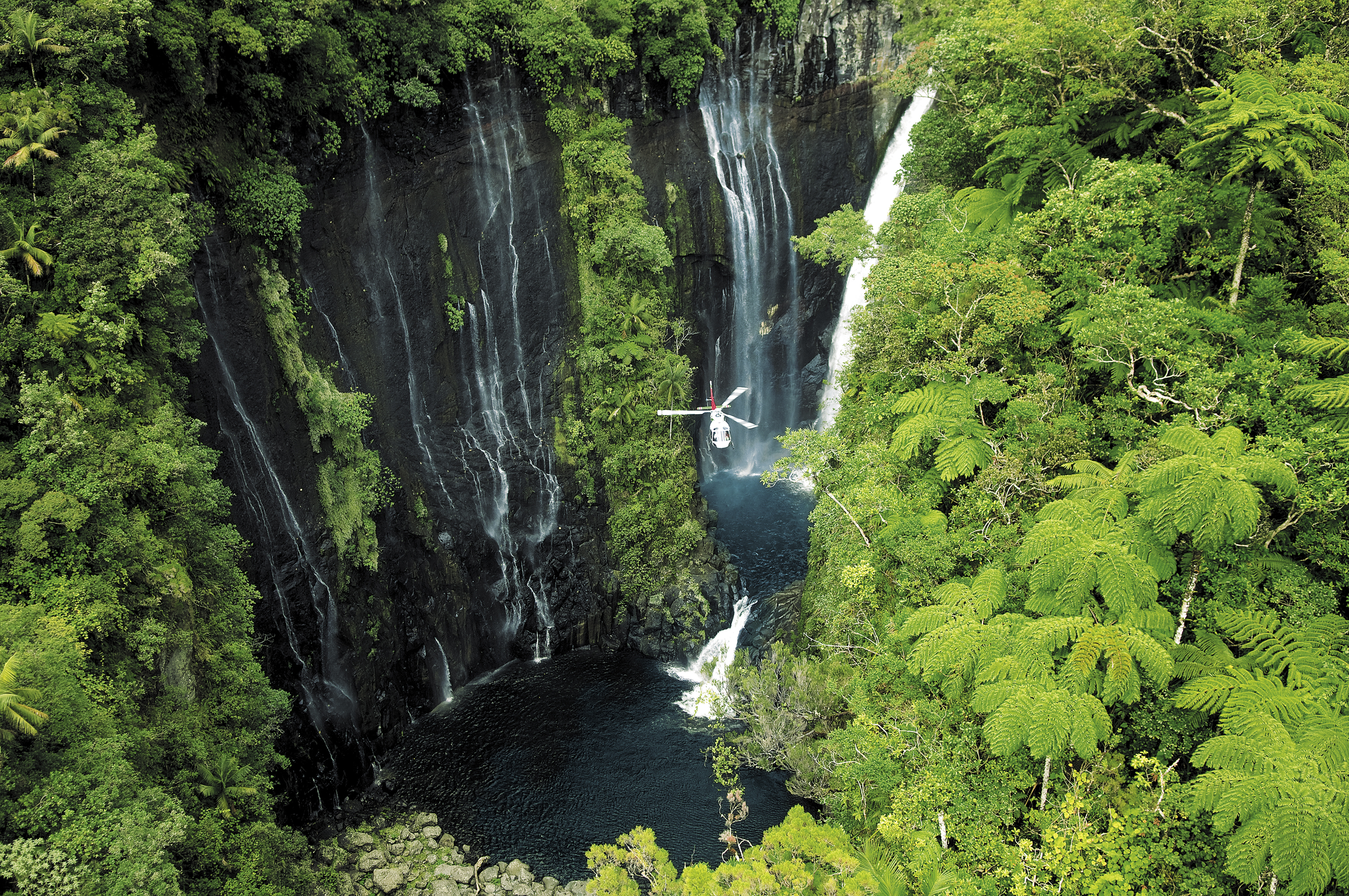 A helicopter flies past the Takamaka waterfalls on Reunion (Serge Gelabert/IRT/PA)