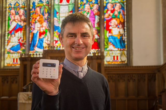 Martyn Taylor, Rector at St George's Church, Stamford, Lincolnshire, holds a contactless payment device.