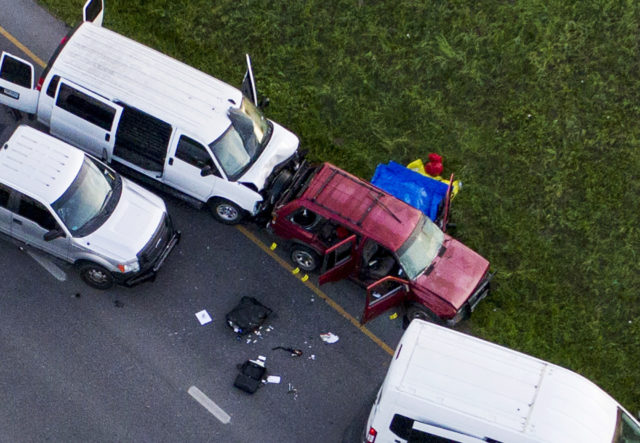 Officials investigate near a vehicle where the suspect blew himself up (Jay Janner/Austin American-Statesman via AP)