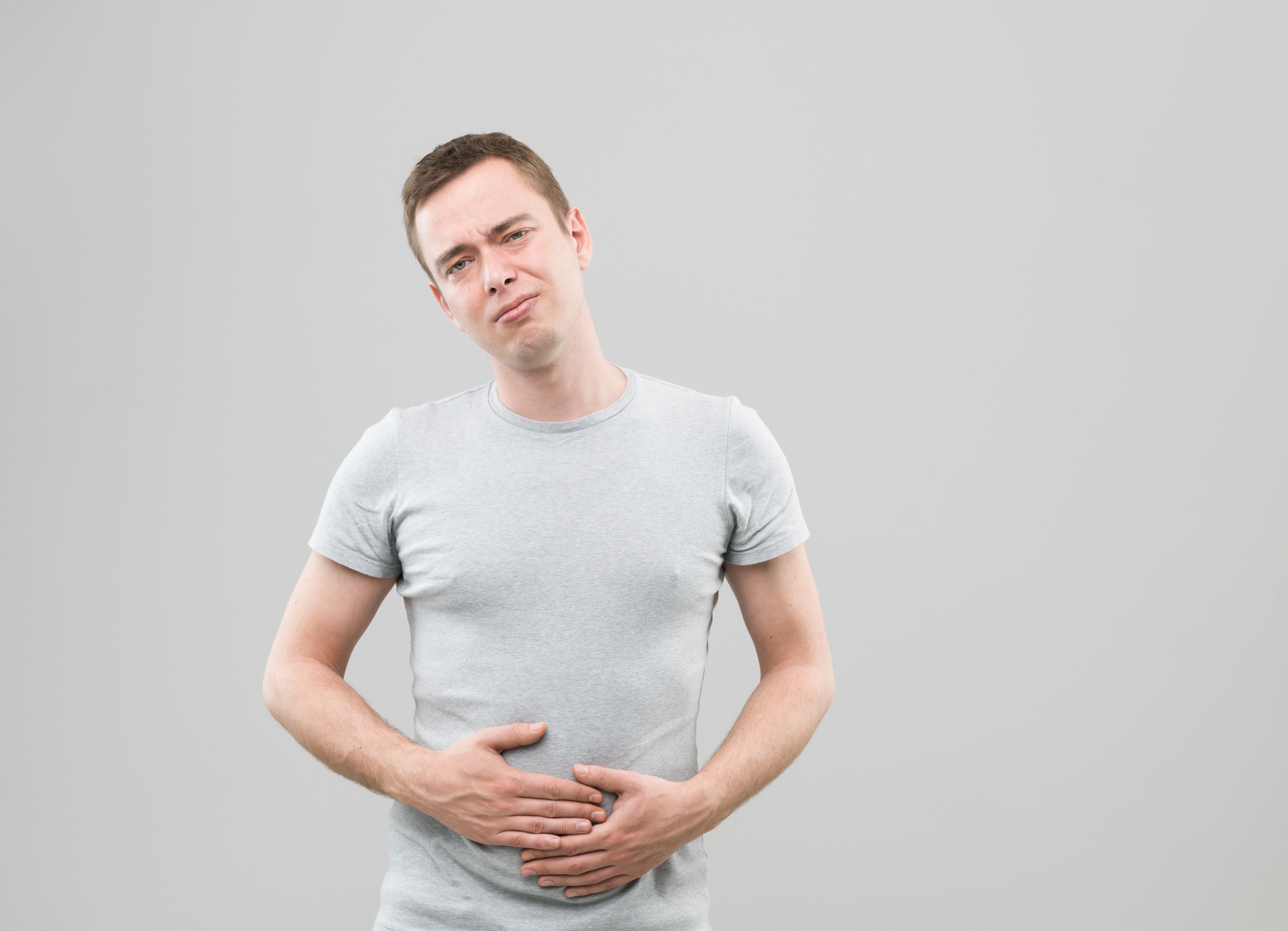 front view of young caucasian man with upset stomach
