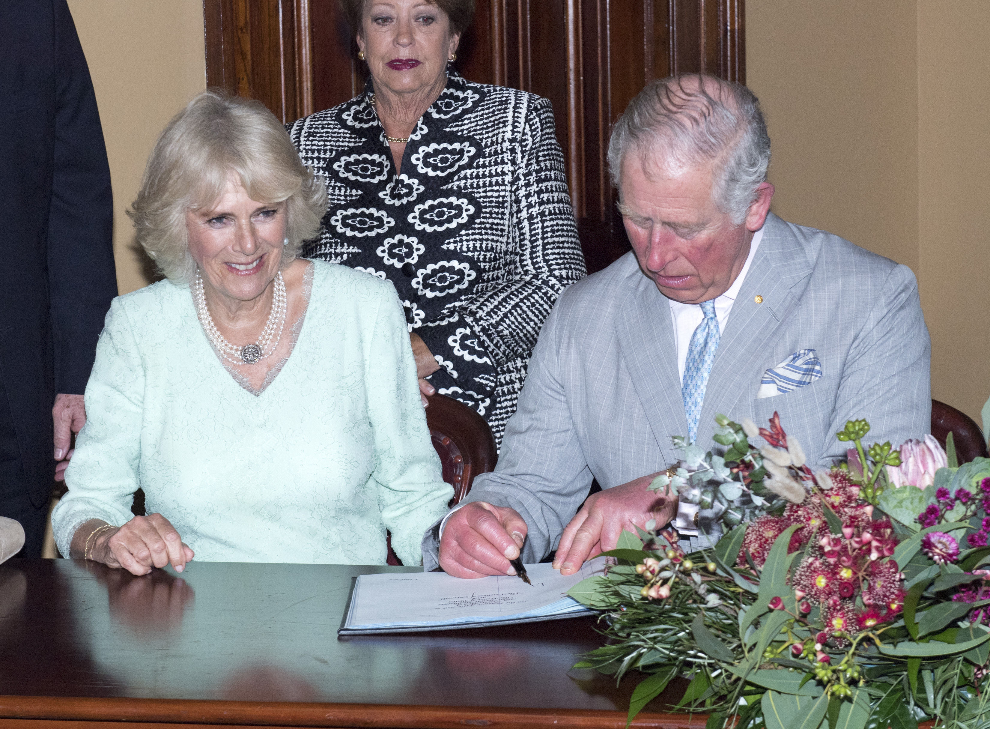 The Prince of Wales and  Duchess of Cornwall sign the visitors' book at Old Government House (Arthur Edwards/The Sun/PA)