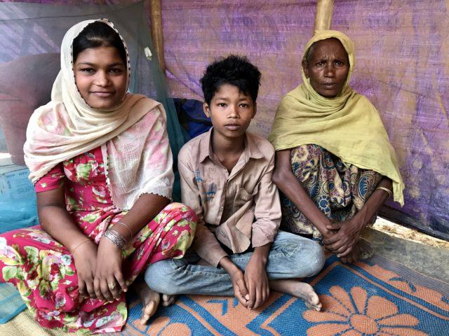 Selim Uddin, 12, with his older sister and his grandmother in their tent in the Balukhali refugee camp, Cox's Bazar (Federica de Caria/PA)