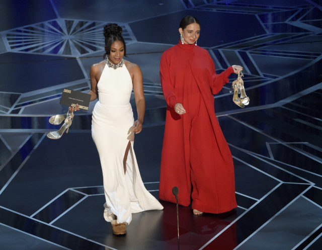 Tiffany Haddish, left, wears the Alexander McQueen dress at the 2018 Oscars alongside Maya Rudolph. (Chris Pizzello/Invision/AP)