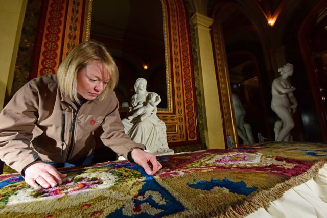 Conservator Caroline Rawson investigates historic clothes moth damage to carpet at Brodsworth Hall in South Yorkshire (English Heritage/PA)