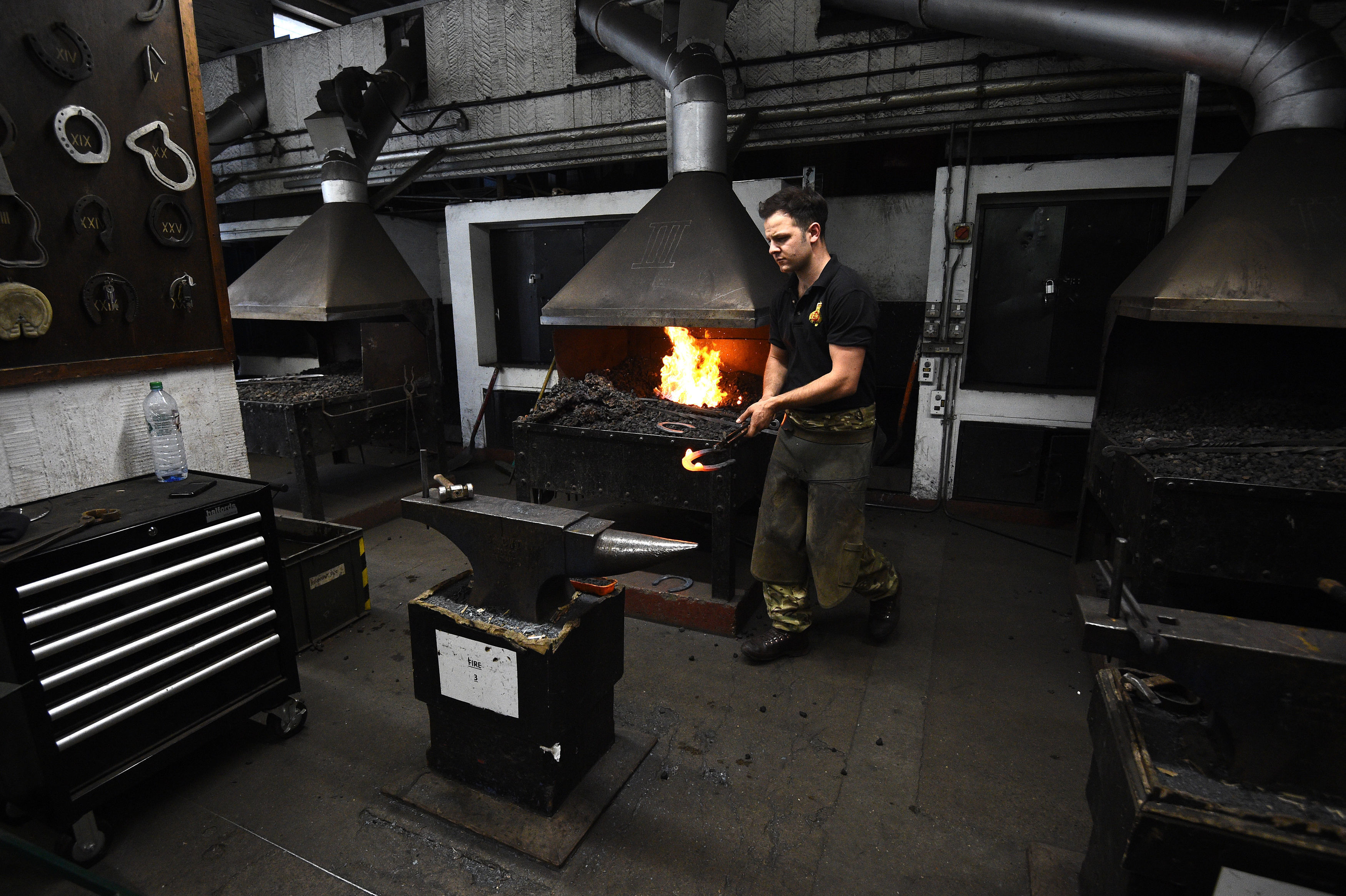 A member of the Household Calvary forges a horse shoe in the forge (Kirsty O'Connor/PA)