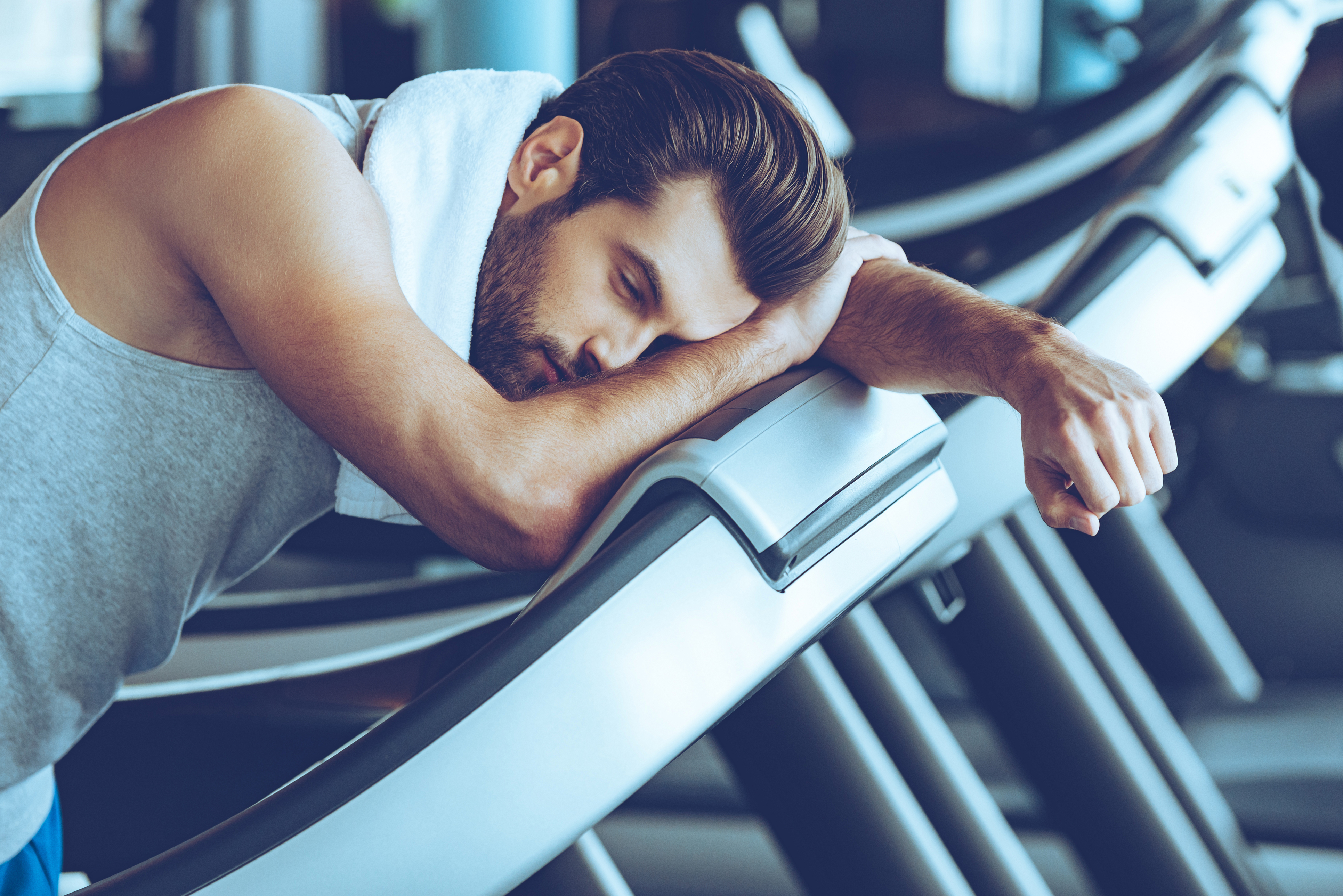 Side view of young man in sportswear looking exhausted while leaning on treadmill at gym