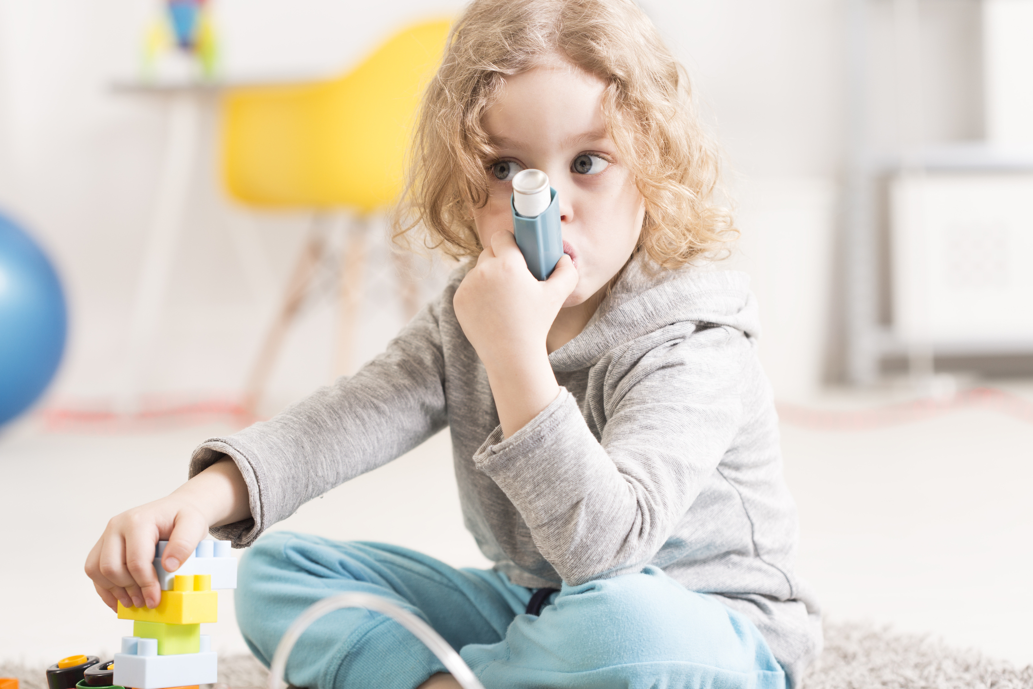 Cropped shot of a small girl sitting on a floor and using her inhaler