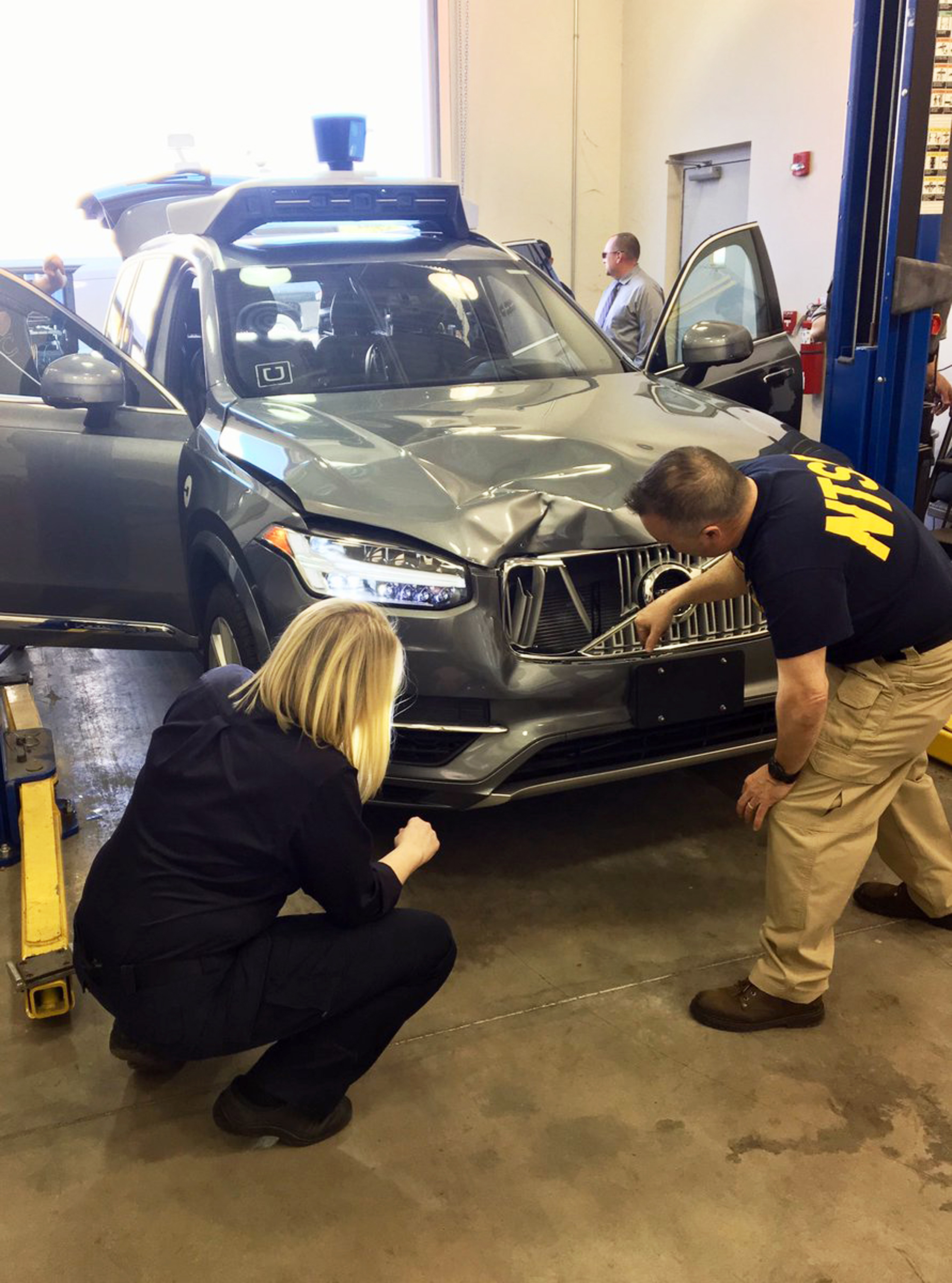 Investigators examine a driverless Uber SUV that fatally struck a woman in Arizona (National Transportation Safety Board via AP)