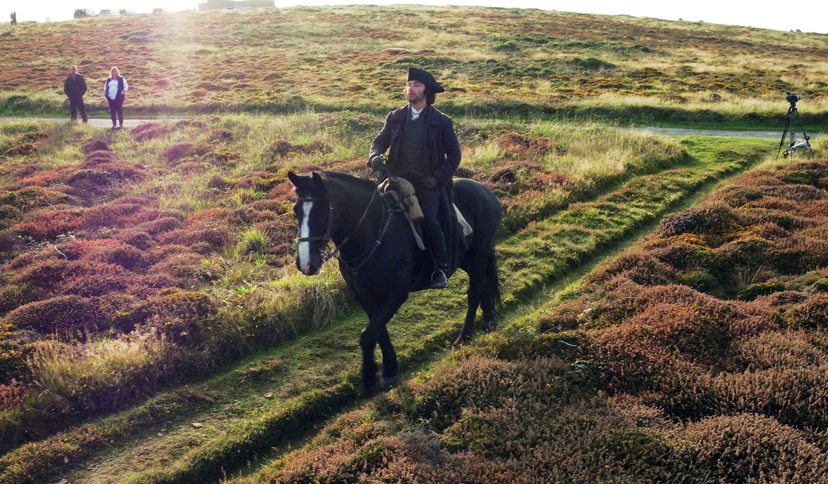 Aidan Turner rides Seamus over heathland on Gwennap Head on the Cornish coast during filming