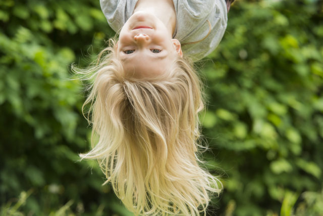 Girl upside -down playing outdoors