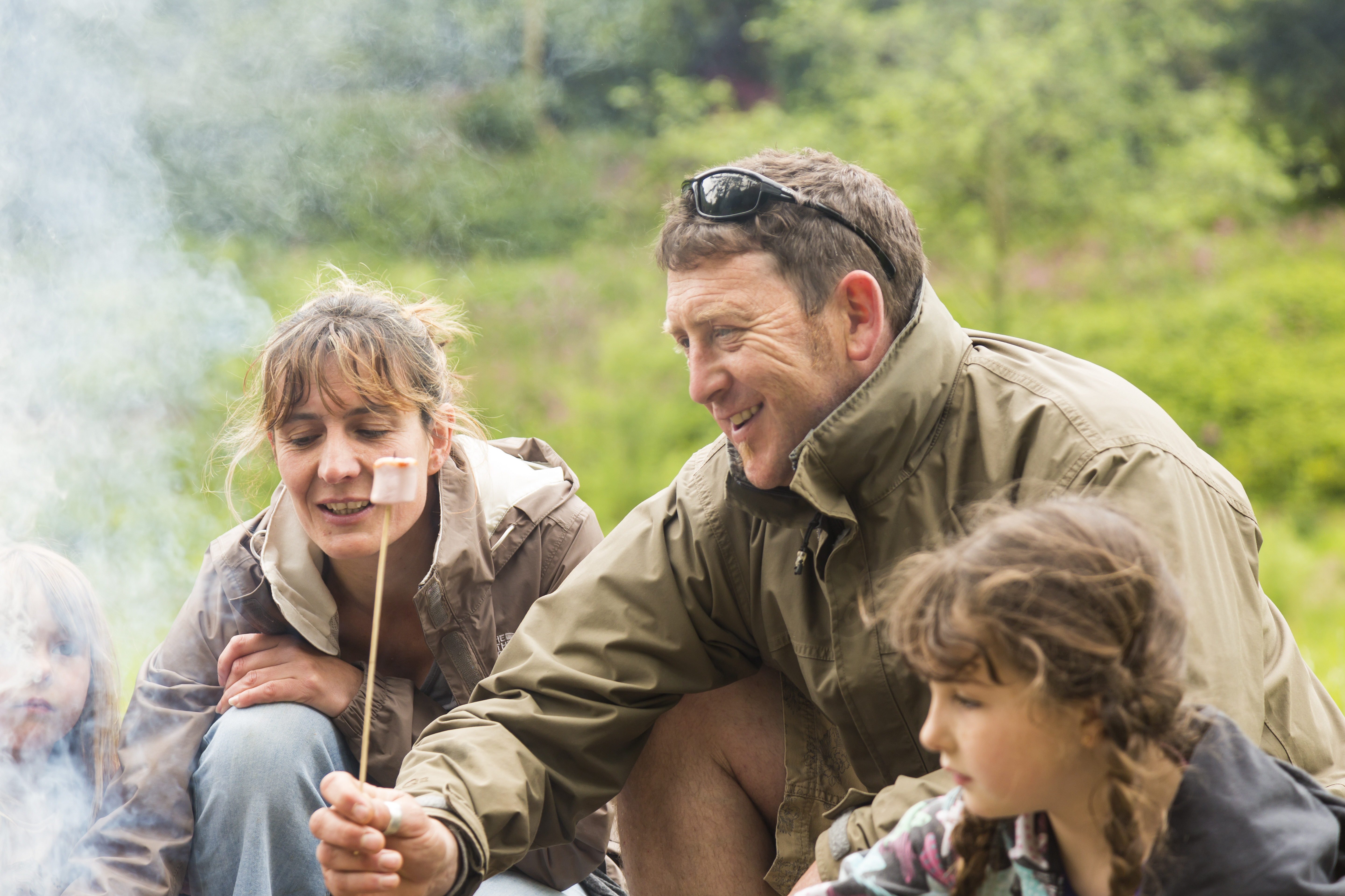 A family toasting marshmallows over an open camp fire at Colby Woodland Garden, Pembrokeshire. The garden is named after Welsh landowner John Colby (1751-1823), who originally came to the area in the 1790s to mine coal. Today, the woodland garden features a wild flower meadow, stream, and colourful walled garden.
