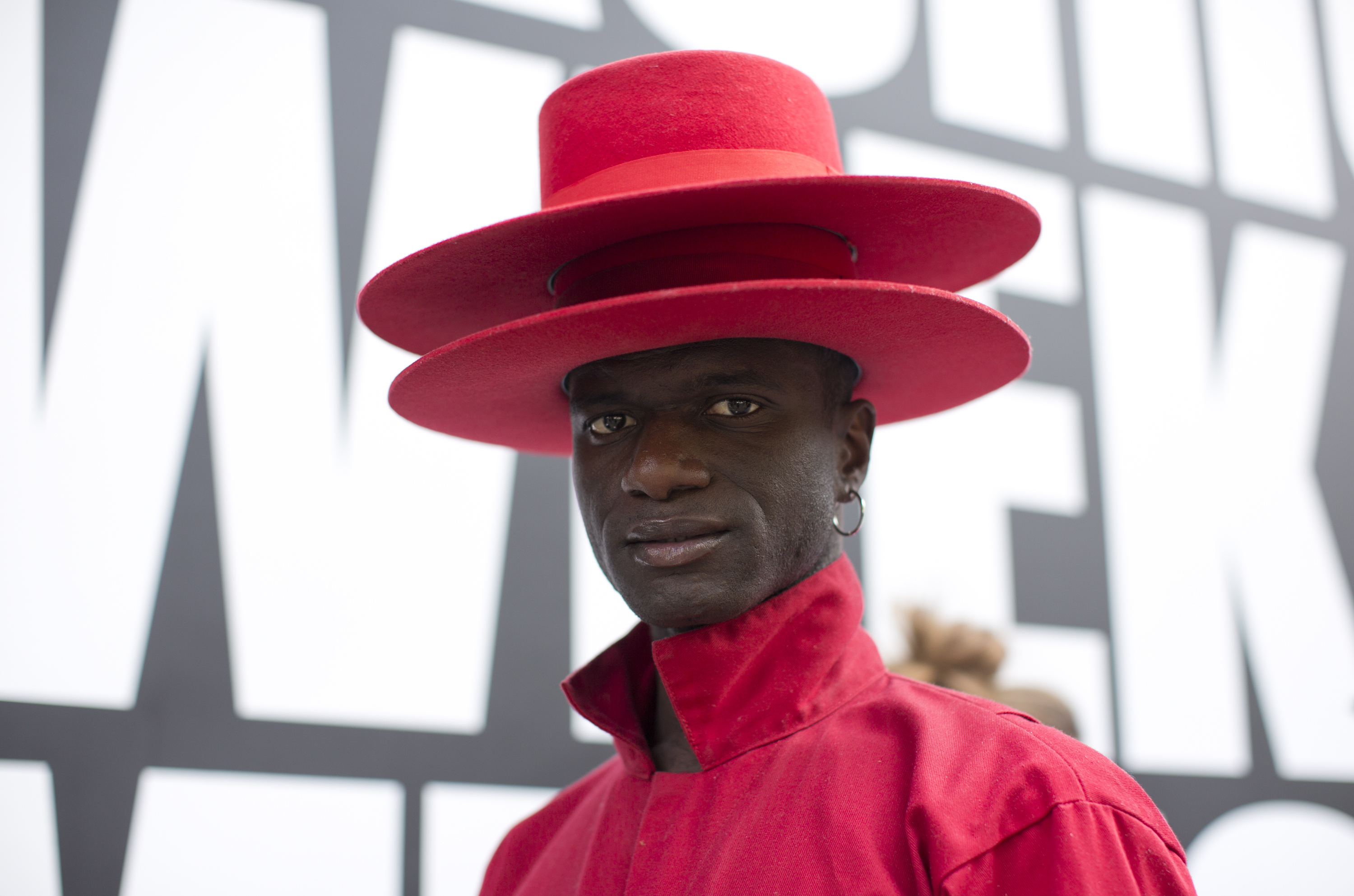 Fashion stylist Abdel Keita Tavares, from Guinea-Bissau, wears a red long sleeve jumpsuit from Dickies outside the BFC Showspace during London Fashion Week Men's SS19.