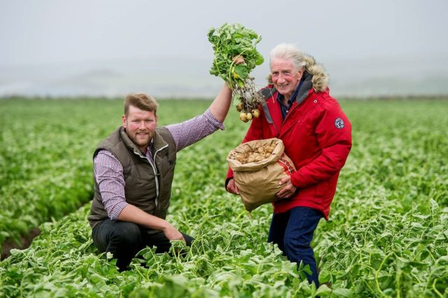 Farmer David Young with Jamie McCoo and his batch of potatoes (Peter Sandground/PA)