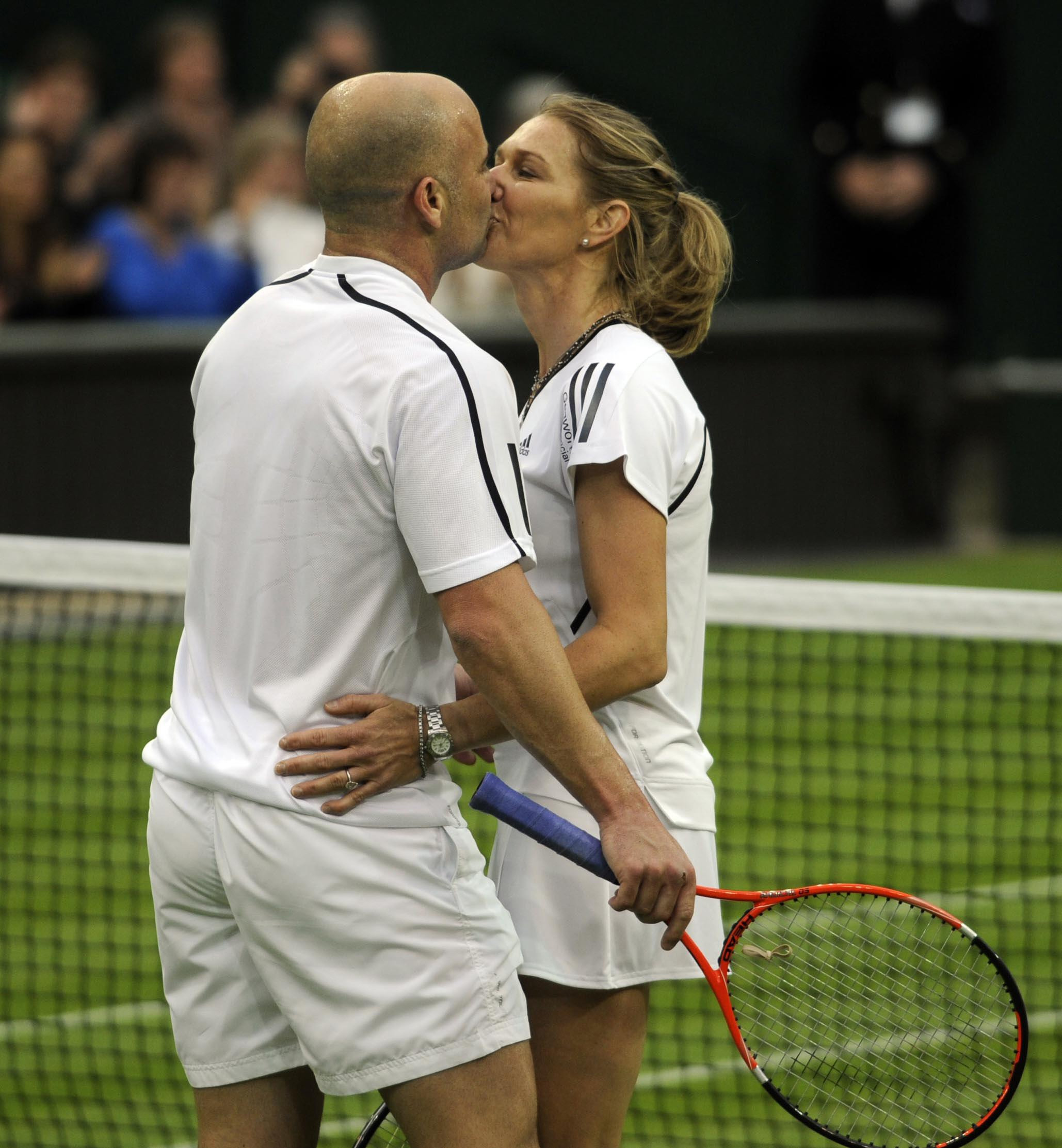 Former Wimbledon champion Steffi Graf kisses her husband and partner Andre Agassi (left) at the end of an exhibition match against Great Britain's Tim Henman and Kim Clijsters on centre court, during the Centre Court Celebration at The All England Lawn Tennis and Croquet Club, Wimbledon, London in 2009. (Rebecca Naden/PA)