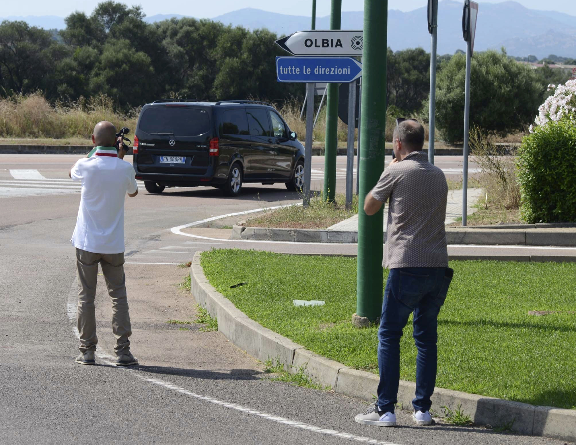 Reporters film a black van leaving the John Paul II hospital in the Sardinian town of Olbia