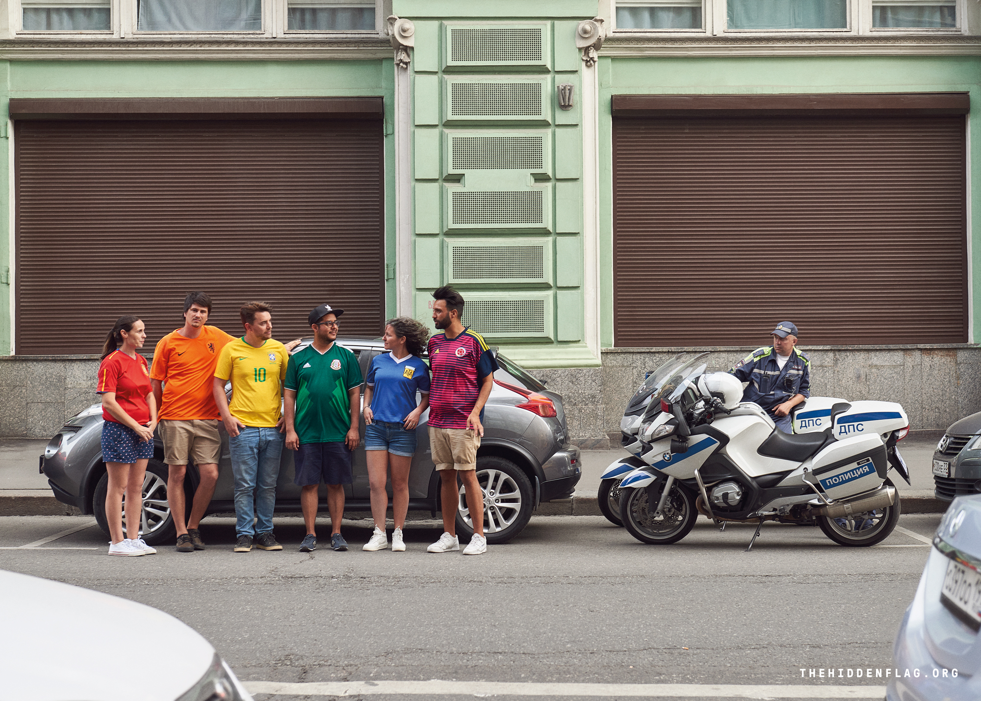 Six activists wear six football shirts to create the colours of the rainbow flag