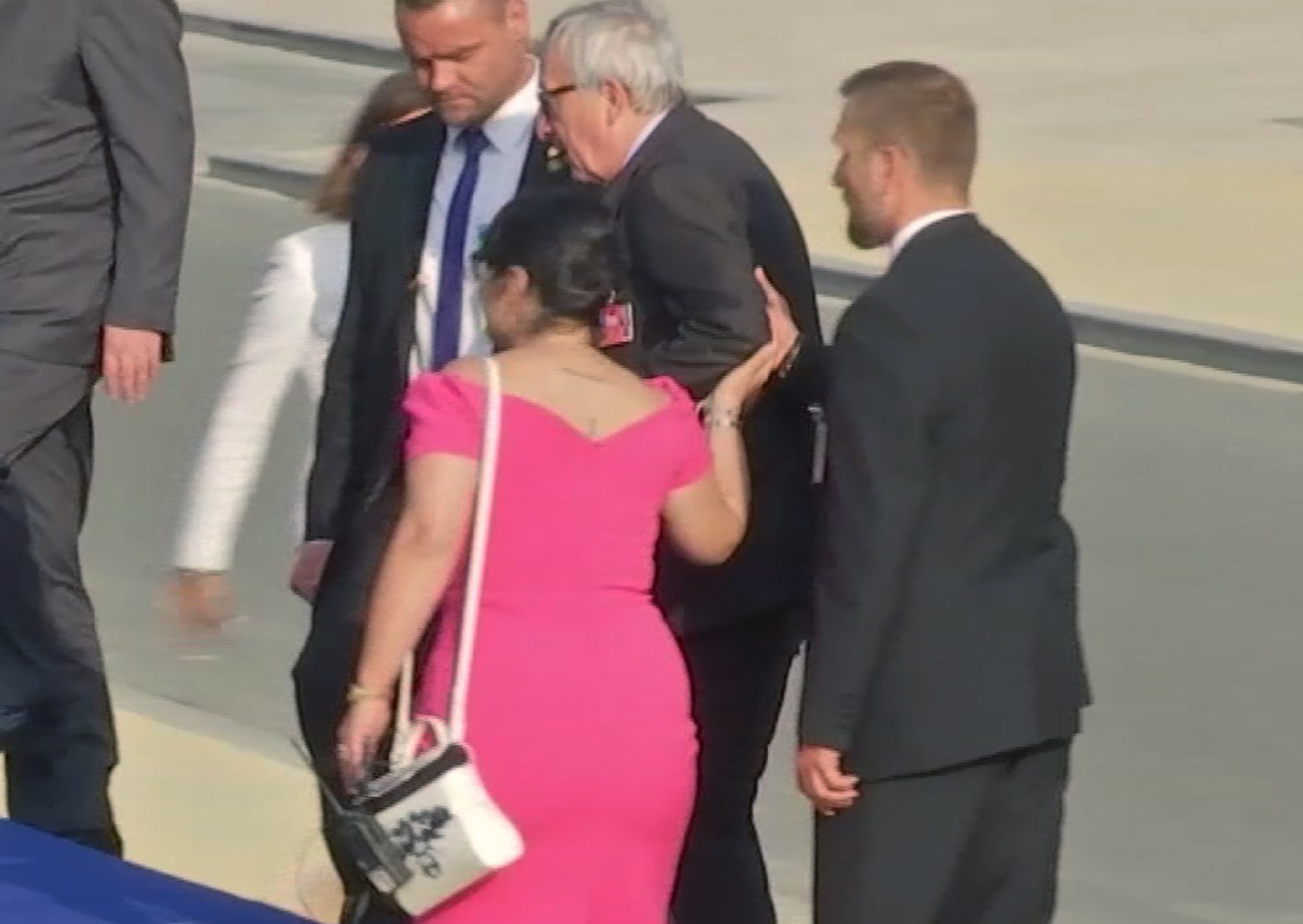 Jean-Claude Juncker is helped up the stairs at Parc Cinquantenaire in Brussels