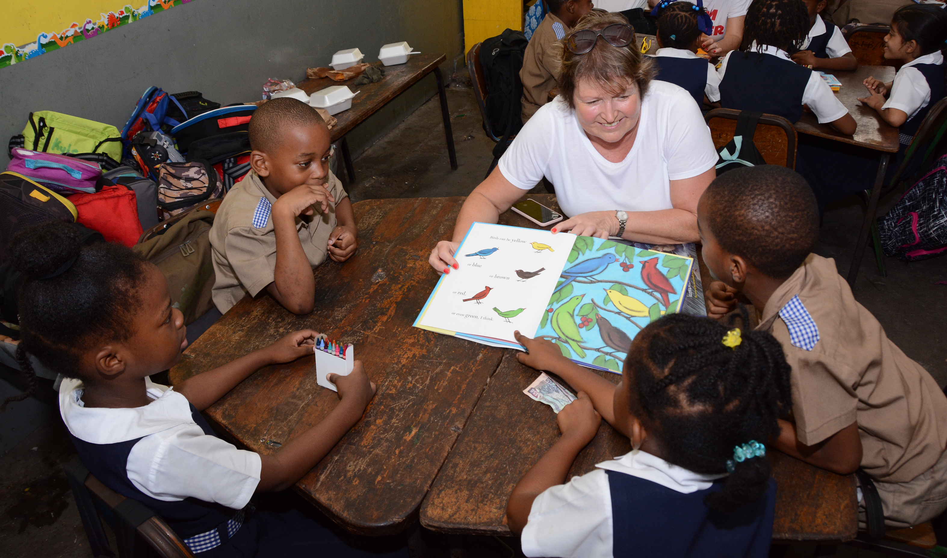 Hannah helps pupils read on a reading road trip excursion (Sandals Resorts/PA)