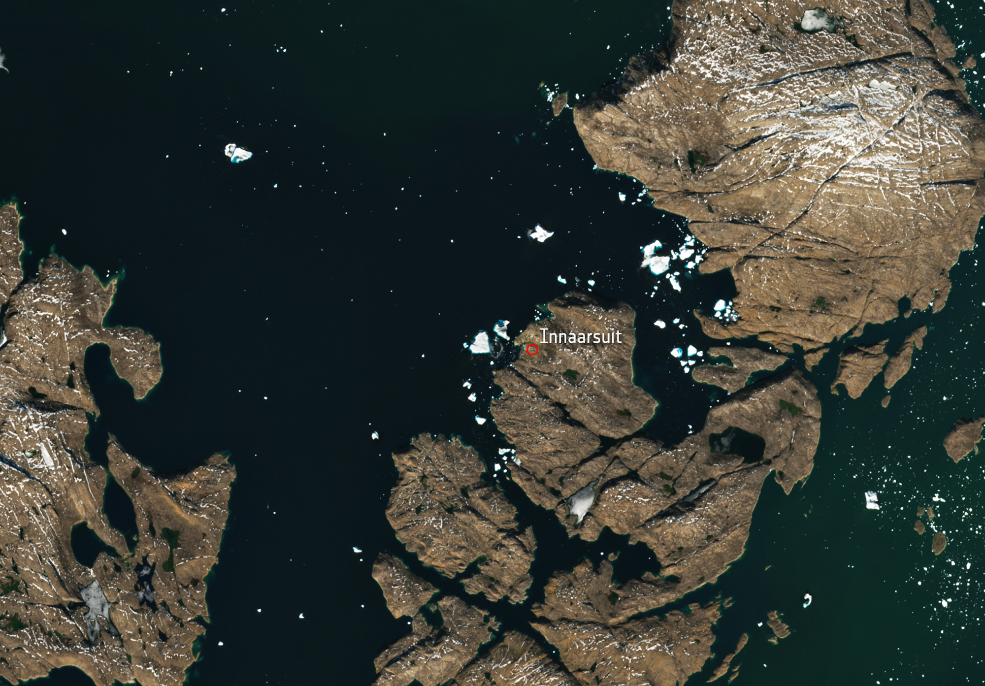 A satellite image shows a huge iceberg perilously close to the village of Innaarsuit