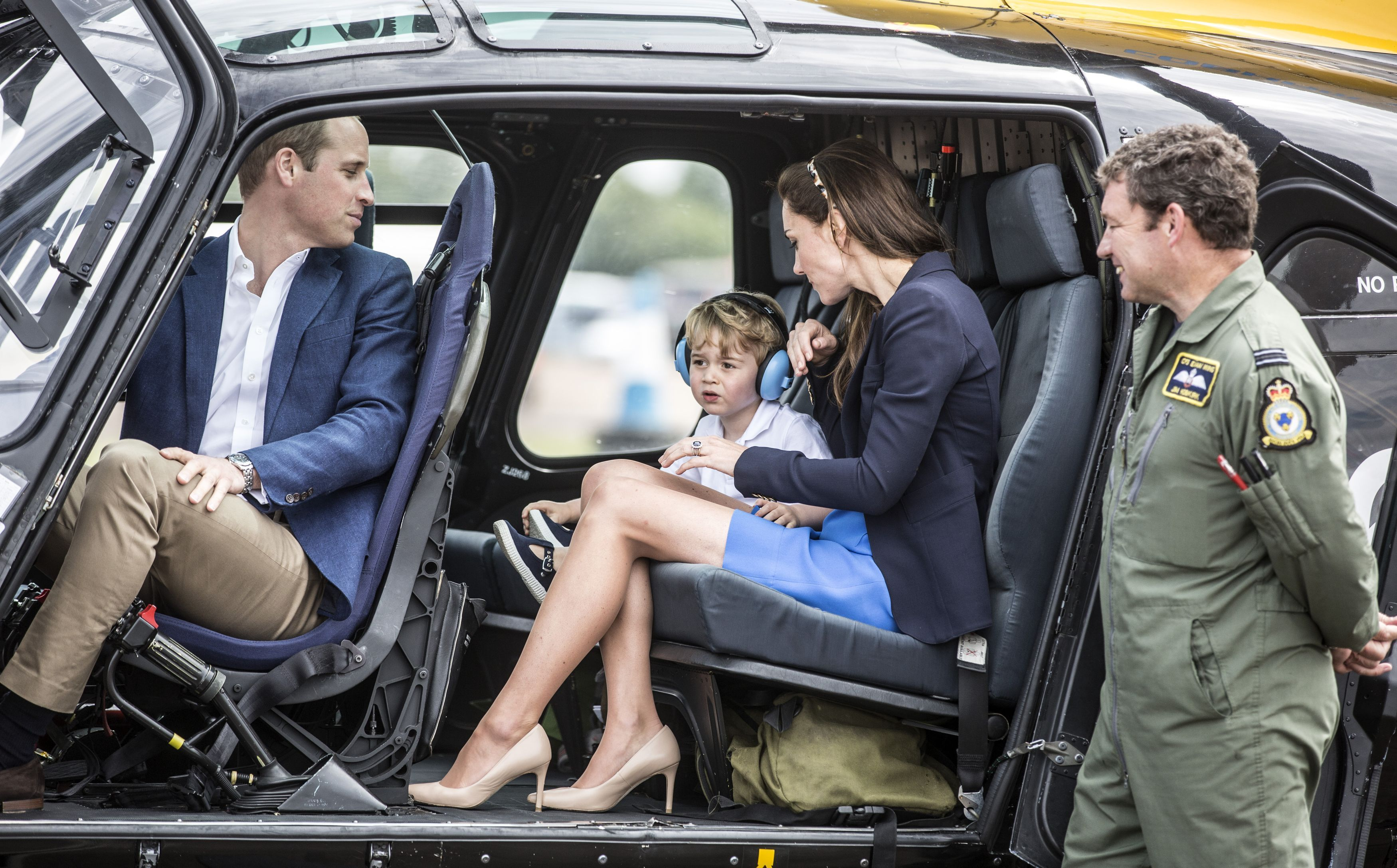 Prince George sits in a Squirrel helicopter with his parents the Duke and Duchess of Cambridge during a visit to the Royal International Air Tattoo at RAF Fairford - the world's largest military airshow
