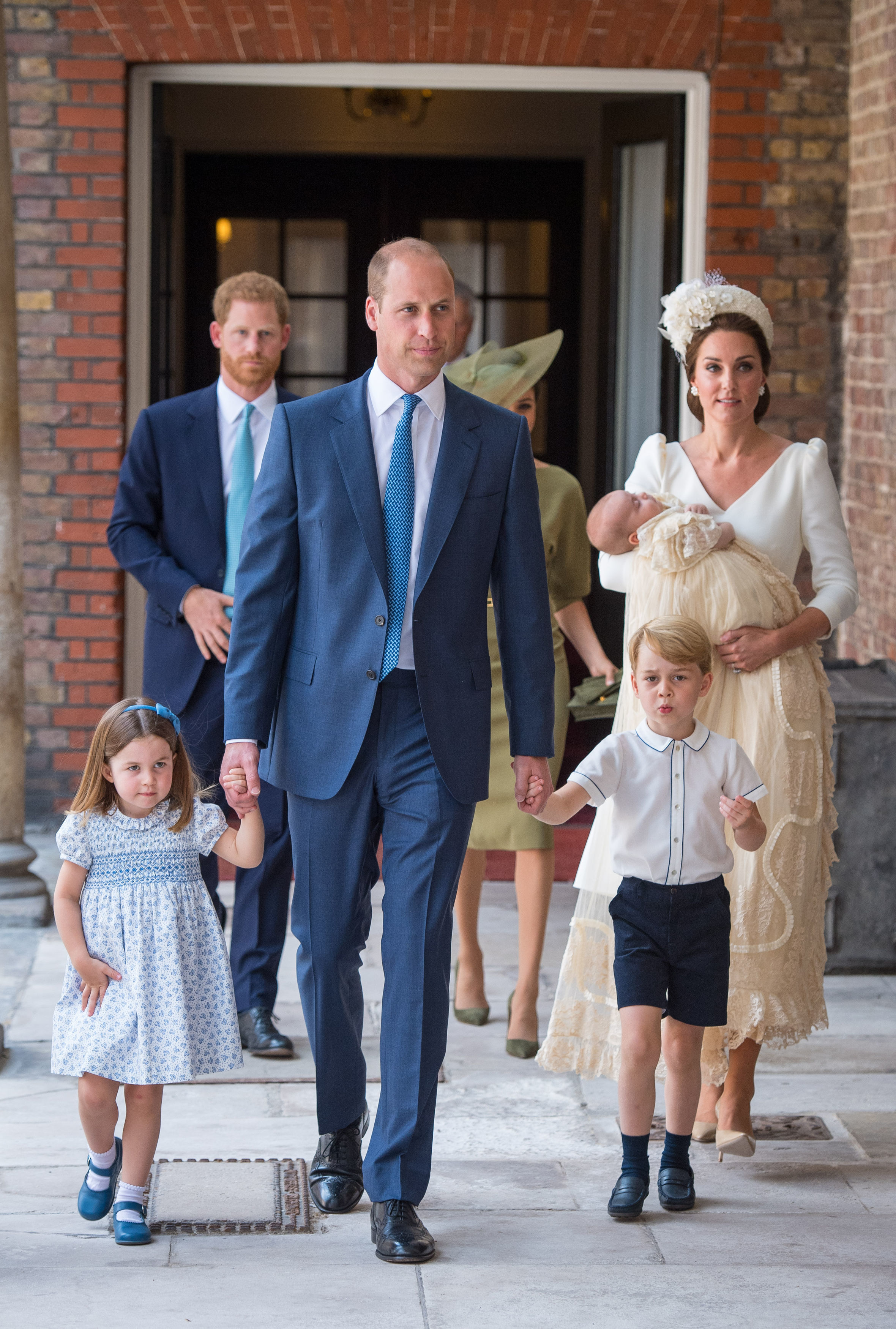 Princess Charlotte and Prince George hold the hands of their father, the Duke of Cambridge, as they arrive at the Chapel Royal, St James's Palace, London for the christening of their brother, Prince Louis, who is being carried by their mother, the Duchess of Cambridge