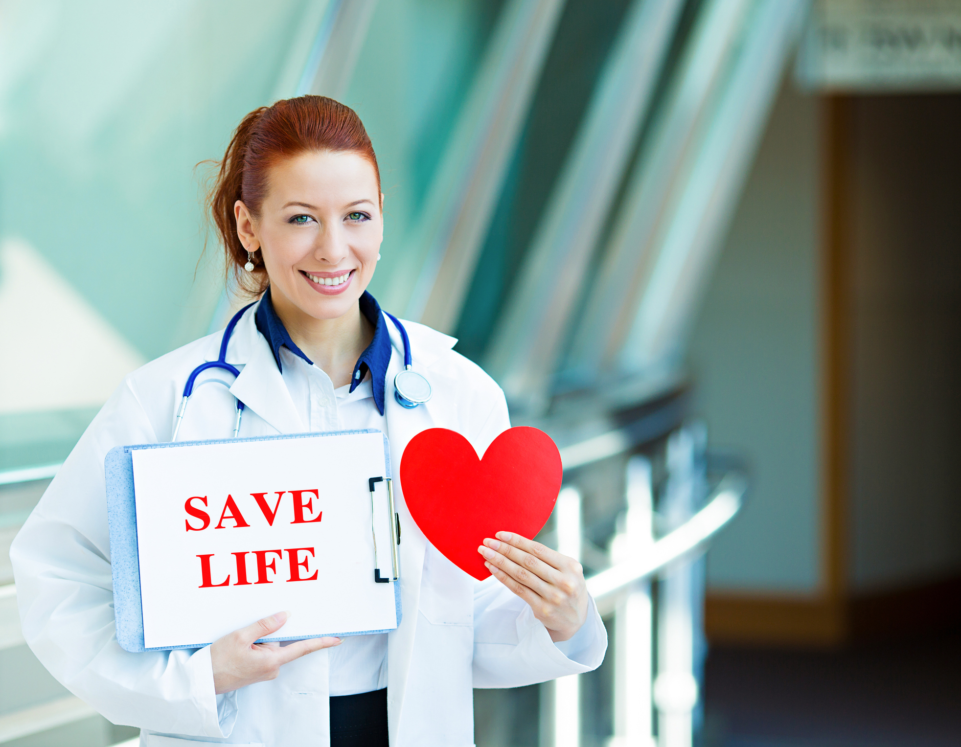 Closeup portrait happy smiling health care professional, woman transplantation medicine doctor, cardiologist with stethoscope holding sign save life, heart isolated hospital hallway background.
